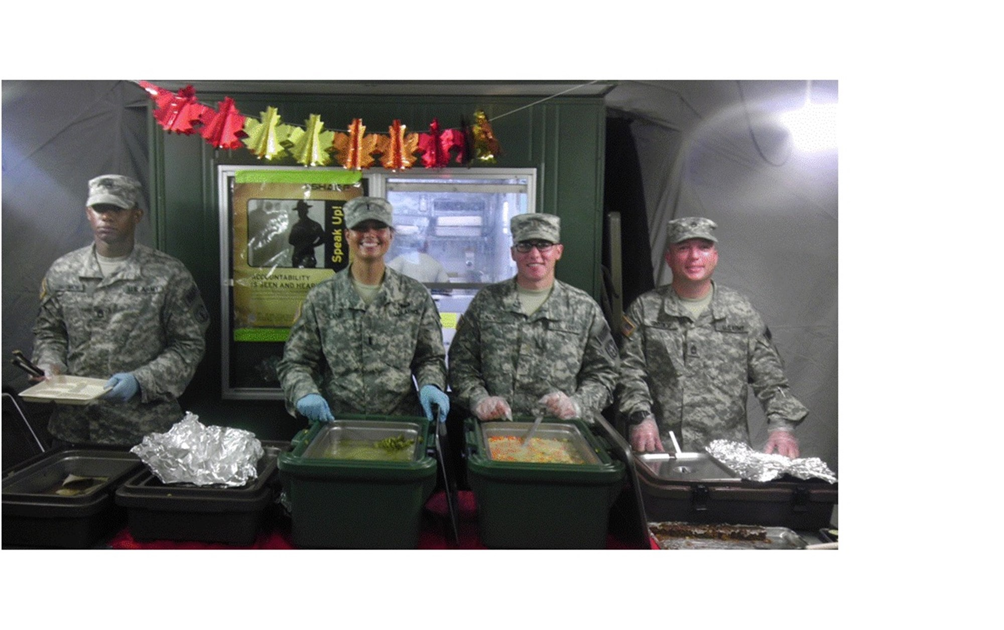 Soldiers serve a hot Thanksgiving Day meal to fellow service members and support personnel. Deliberate planning and actions across the entire logistics enterprise united the efforts of a multi-disciplined, interagency team formed across nations, governments and non-government organizations (NGOs) which directly led to success in OPERATION United Assistance. (U.S. AFRICOM photo/released)
