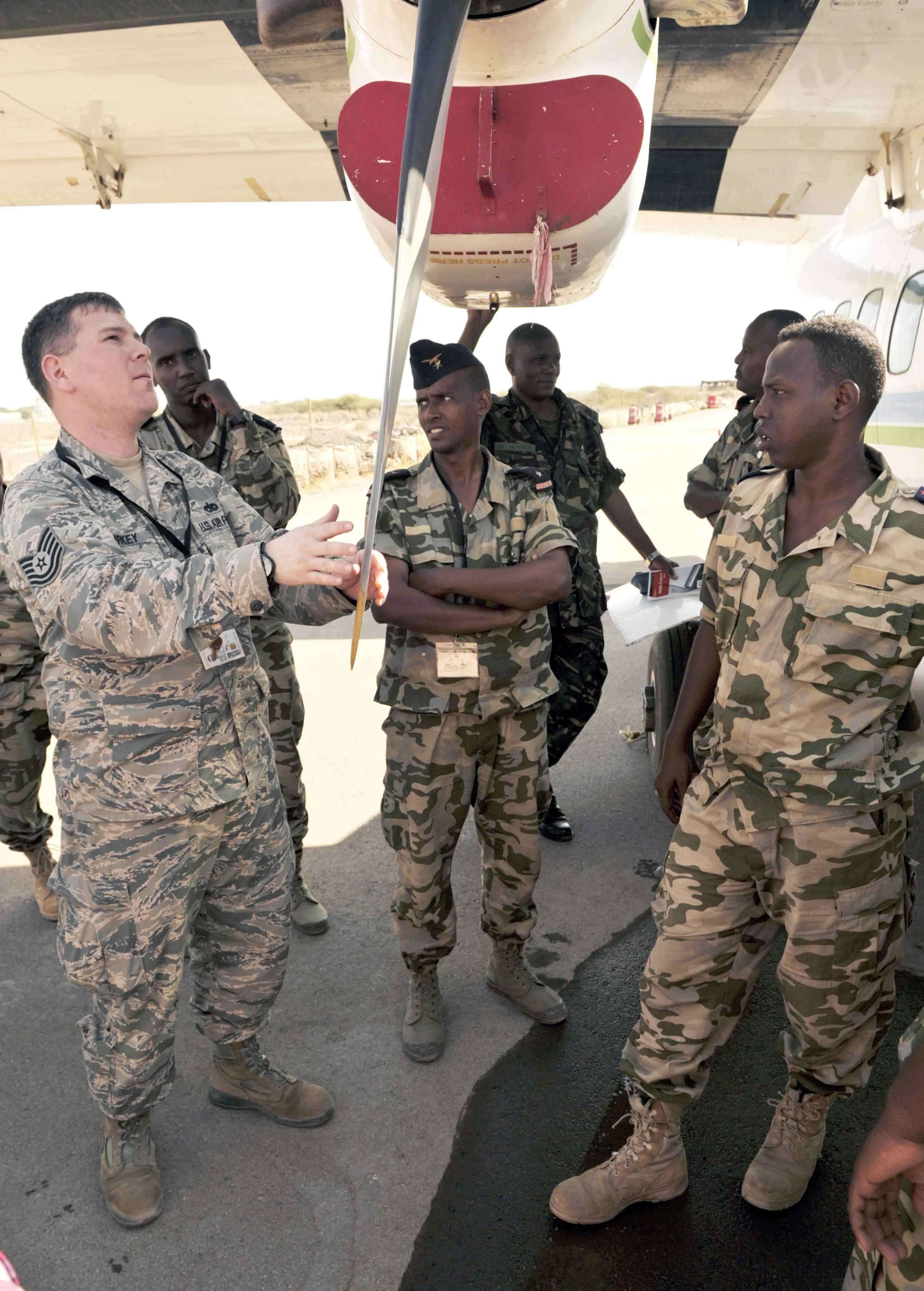 U.S. Air Force Tech. Sgt. Albert Kirkey, 818th Mobility Support Advisory Squadron aircraft maintenance advisor, talks with Djiboutian air force members about maintenance procedures for the Let L-410 Turbolet aircraft during African Partnership Flight–Djibouti at Djibouti Air Base, Feb. 9, 2015.  APF is the premiere program to bring together partner nations to increase cooperation and interoperability, which fosters stability and security throughout the continent. (U.S. Air Force Photo by Tech. Sgt. Ian Dean)