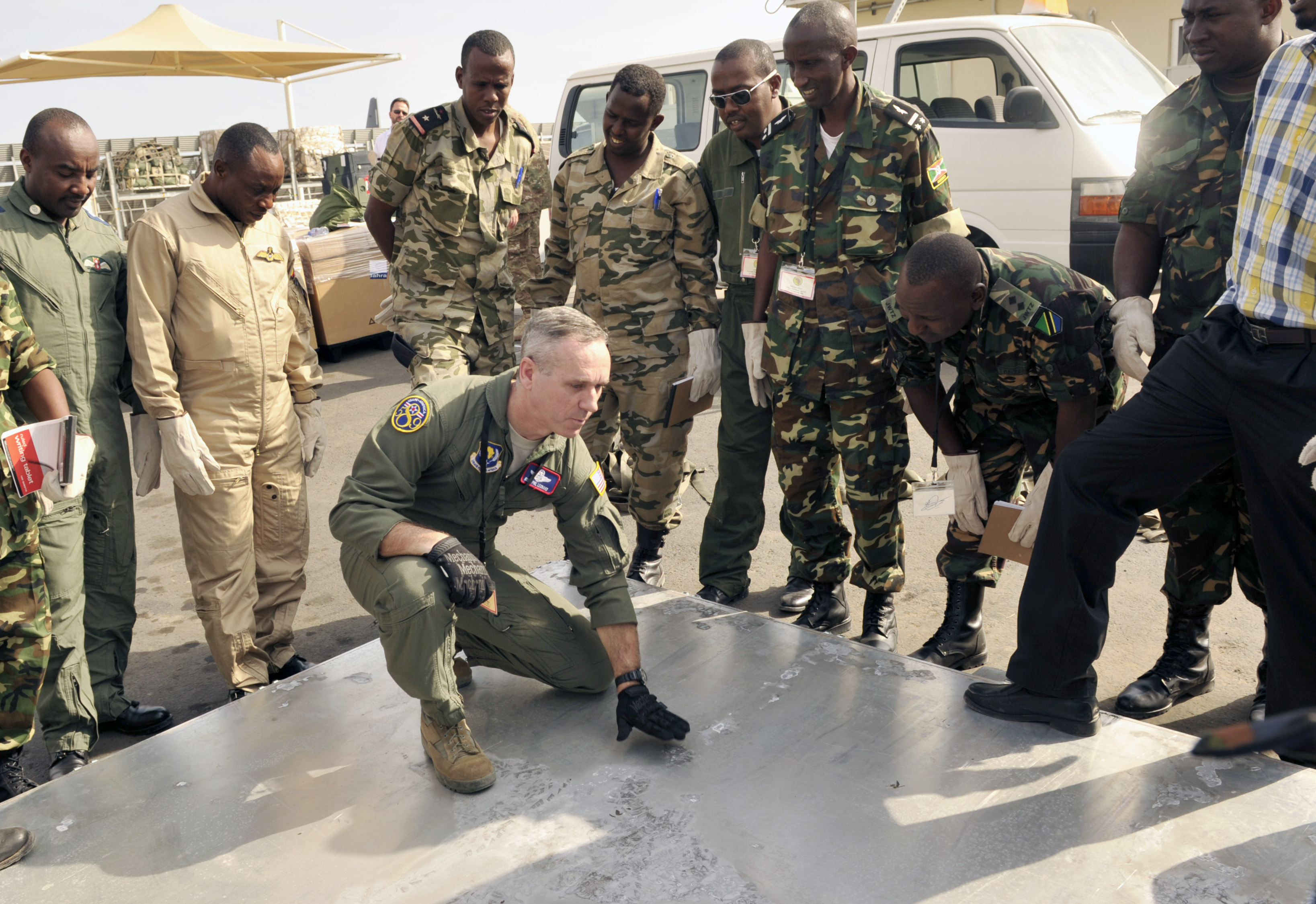 U.S. Air Force Senior Master Sgt. Phillip Leonard, U.S. Air Forces Europe and Air Forces Africa loadmaster, discusses cargo pallet inspection procedures with East African air forces members during African Partnership Flight– Djibouti at Djibouti Air Base, Feb. 10, 2015.  APF is the premiere program to bring together partner nations to increase cooperation and interoperability, which fosters stability and security throughout the continent. (U.S. Air Force Photo by Tech. Sgt. Ian Dean)