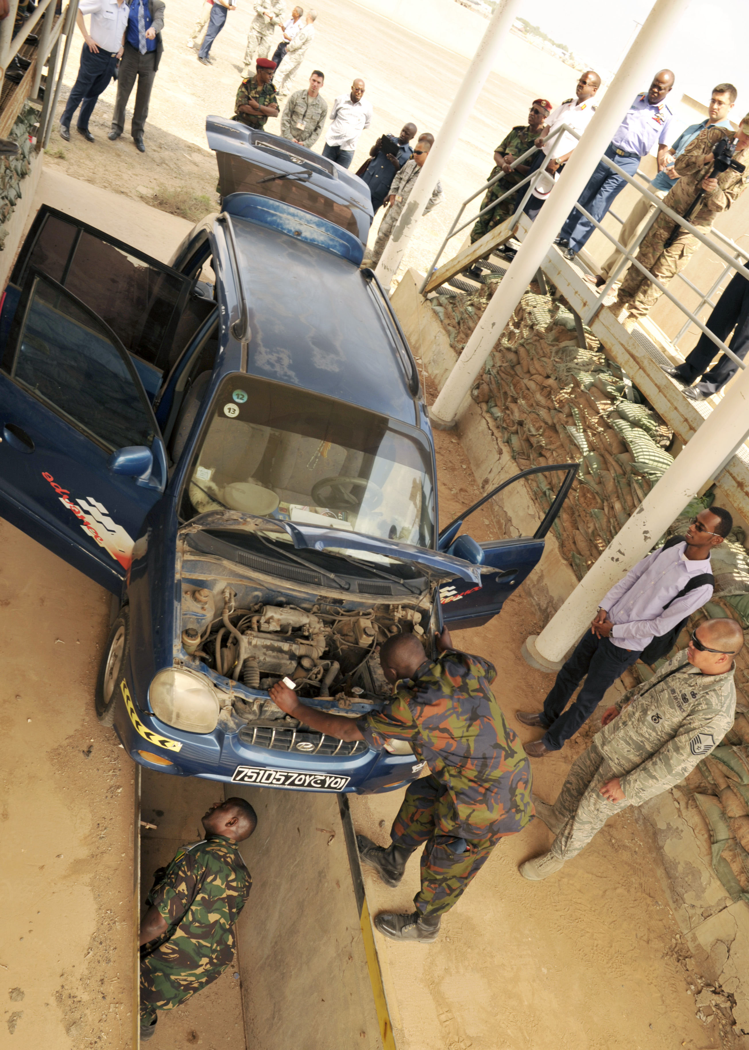 Kenya and Tanzania air force members conduct a vehicle inspection as part of an installation security knowledge exchange during African Partnership Flight–Djibouti at Djibouti Air Base, Feb. 9, 2015.  APF is the premiere program to bring together partner nations to increase cooperation and interoperability, which fosters stability and security throughout the continent. (U.S. Air Force Photo by Tech. Sgt. Ian Dean)