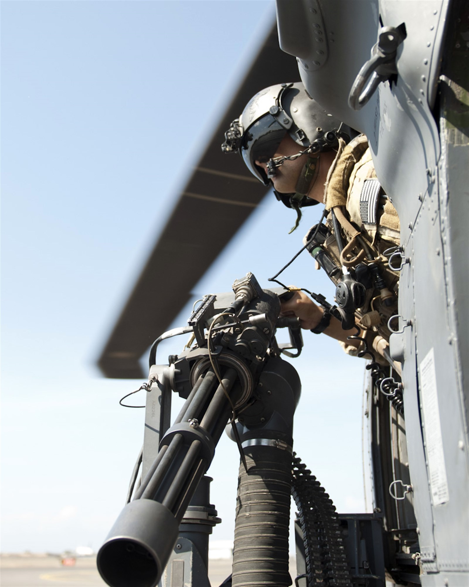 U.S. Air Force Master Sgt. Antonio Jimenez, 303rd Expeditionary Rescue Squadron special mission aviator, glances out of an HH-60 Pave Hawk during a 600-pound weight check at Camp Lemonnier, Djibouti on Jan. 26, 2015. The Weight check was part of the flight inspection to ensure everything is operable prior to a mission. (U.S. Air Force photo by Staff Sgt. Kevin Iinuma)