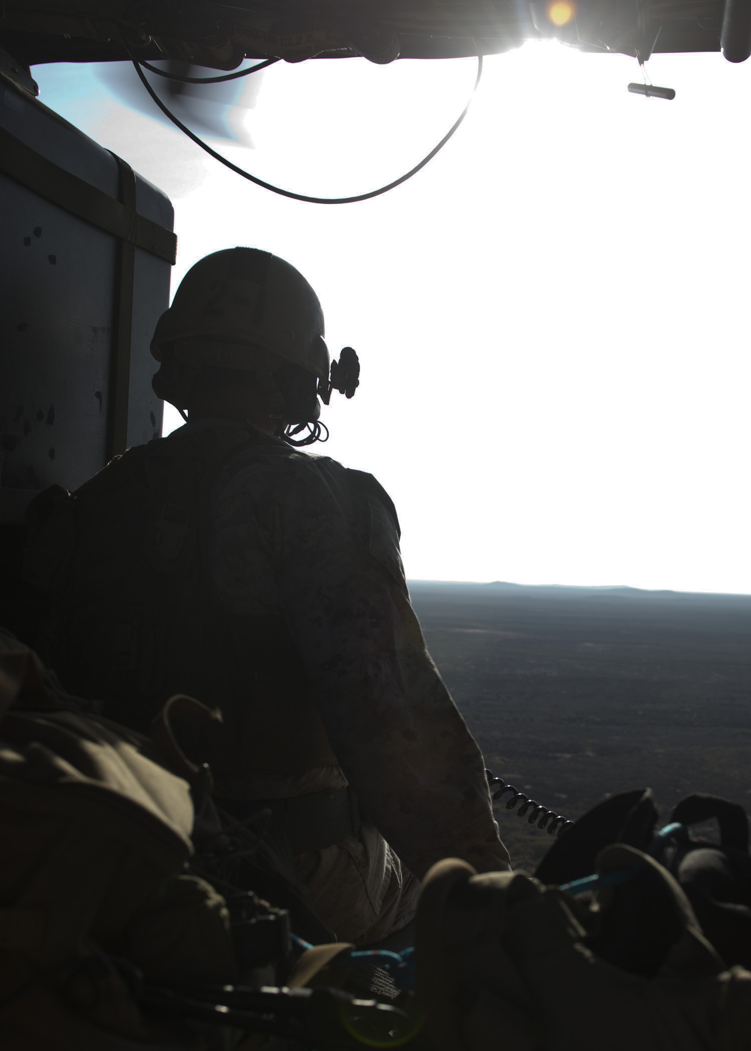 A joint terminal attack controller from the 24th Marine Expeditionary Unit's Maritime Raid Force observes the area below from an Air Force HH-60 Pave Hawk during a flight over Arta, Djibouti, Feb. 4, 2015. The 24th MEU is embarked on the ships of the Iwo Jima Amphibious Ready Group and deployed to maintain regional security in the U.S. 5th Fleet area of operations. (U.S. Air Force photo by Staff Sgt. Kevin Iinuma)