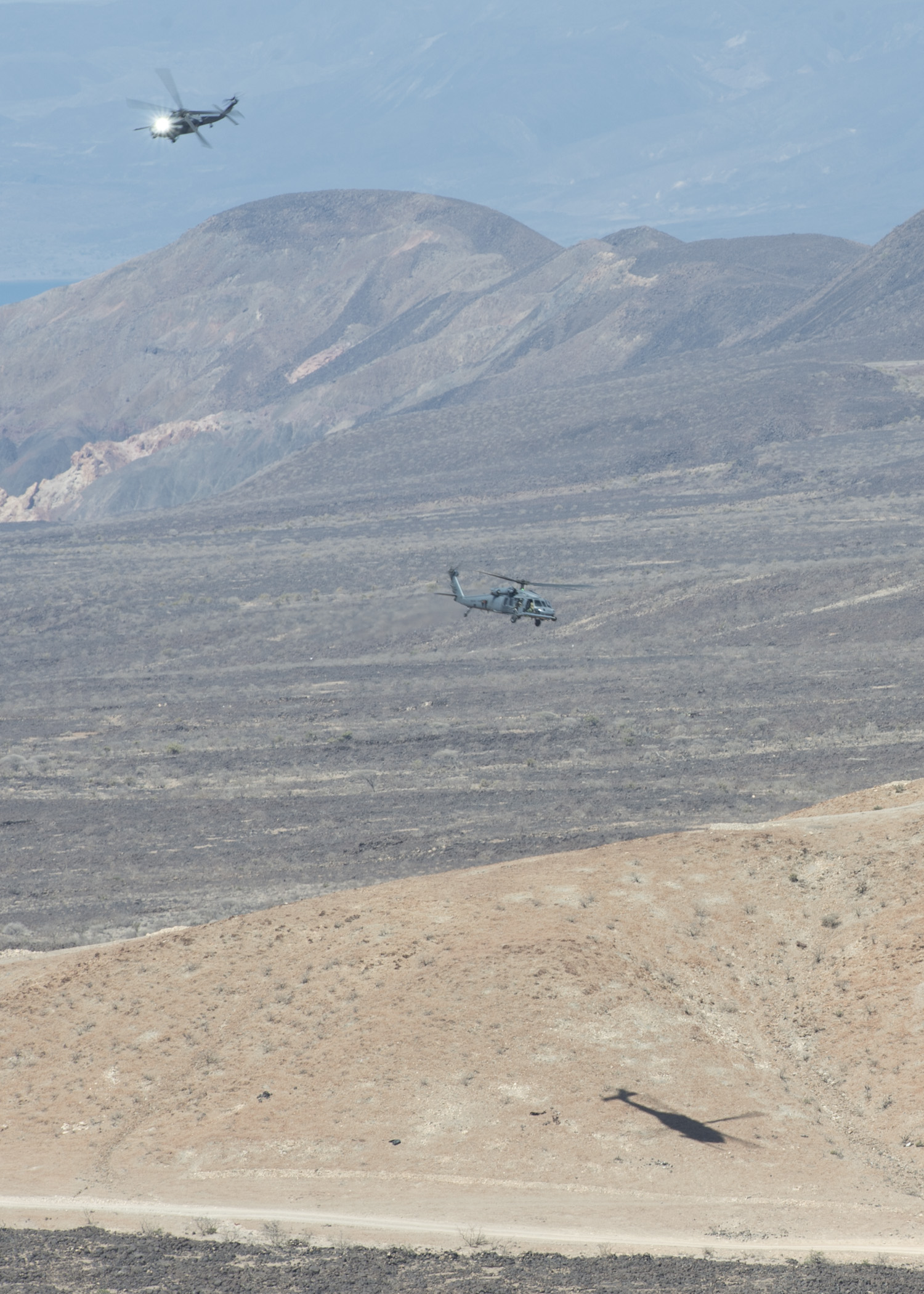 Two U.S. Air Force HH-60 Pave Hawks from the 303rd Expeditionary Rescue Squadron, line their sites on a target called in by U.S. and French joint terminal attack controllers during a bilateral close air support training exercise in Arta, Djibouti, Feb. 4, 2015. The event was part of a scheduled bilateral CAS exercise between a contingent of 24th Marine Expeditionary Unit Marines and French soldiers and sailors. (U.S. Air Force photo by Staff Sgt. Kevin Iinuma)