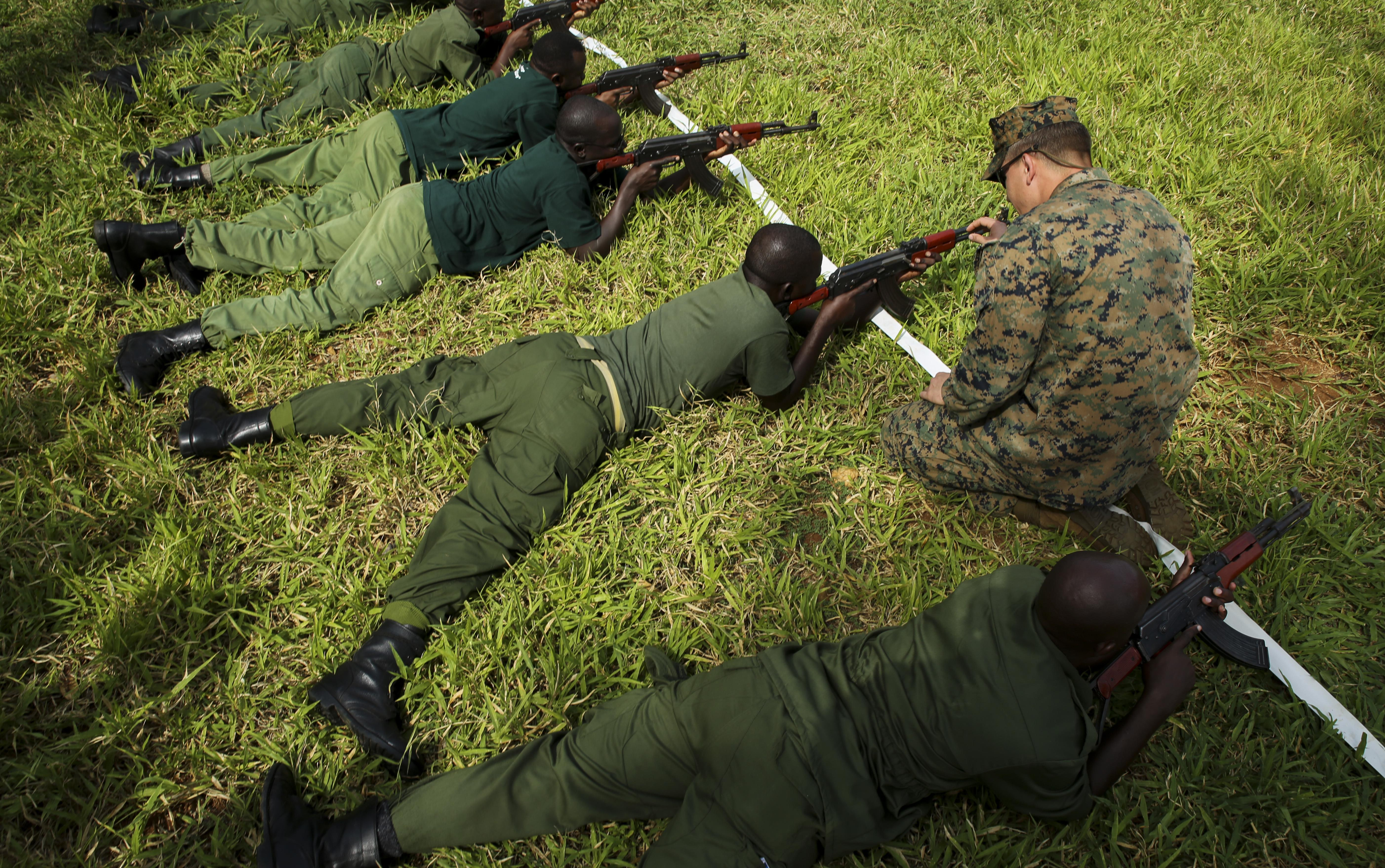 U.S. Marine Sgt. Kyle Kimbriel, right, the noncommissioned officer in charge of the Theater Security Cooperation team with Special-Purpose Marine Air-Ground Task Force Crisis Response-Africa, helps a Tanzanian park ranger aim an AKM assault rifle in the prone position during a combat marksmanship class at the Selous Game Reserve in Matambwe, Tanzania, March 3, 2015. The Marines and Sailors will spend the next several weeks teaching the Tanzanian park rangers infantry skills such as patrolling, offensive tactics, land navigation and mounted operations to aid in countering illicit trafficking. (U.S. Marine Corps photo by Lance Cpl. Lucas J. Hopkins/Released)