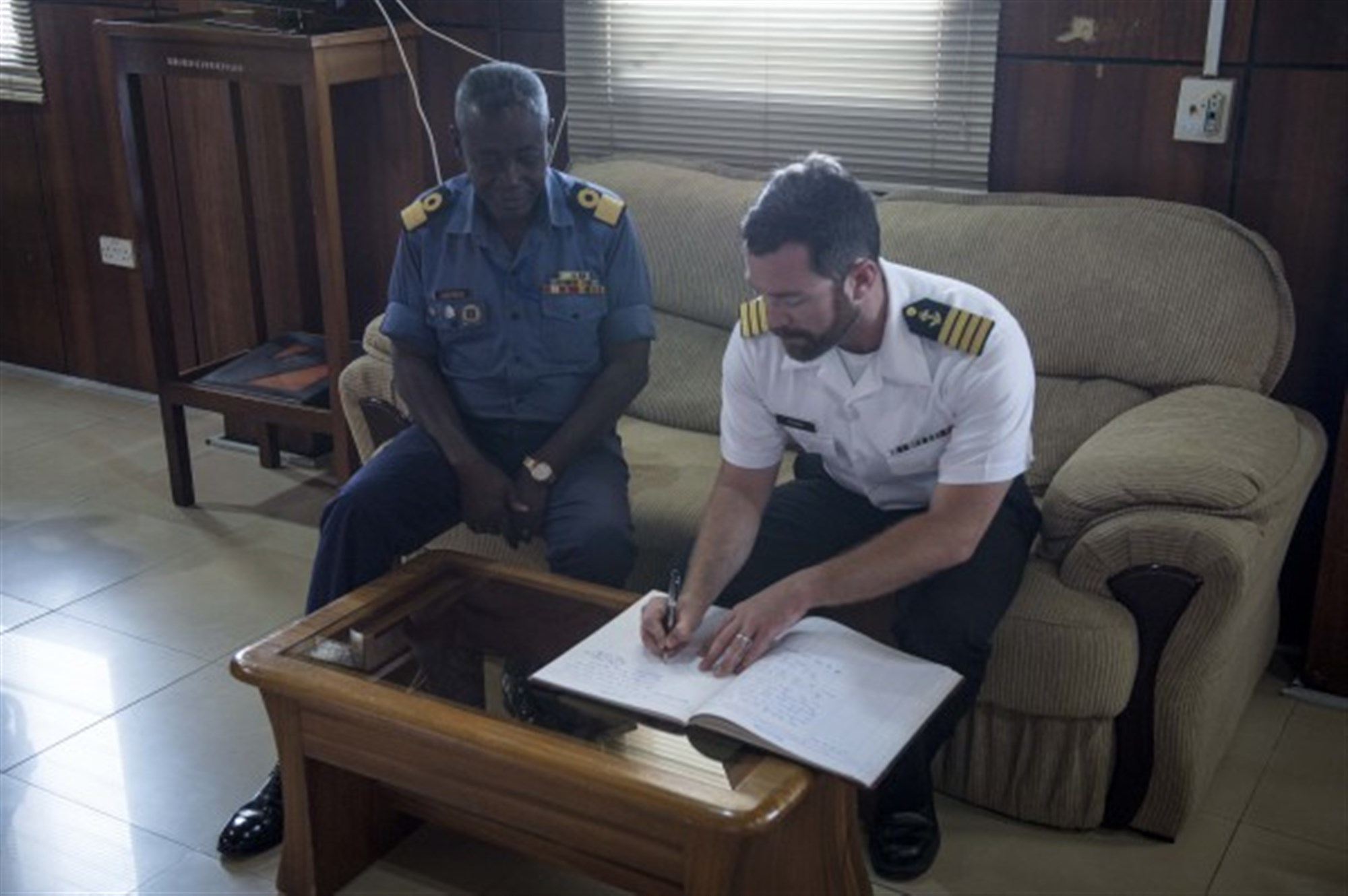 Capt. James Regan, ship's master of the Military Sealift Command's joint high-speed vessel USNS Spearhead (JHSV 1), right, signs the official guest registry of Commodore Steve Darbo of Ghanaian navy March 26, 2015. Spearhead is on a scheduled deployment to the U.S. 6th Fleet area of operations in support of the international collaborative capacity-building program Africa Partnership Station. (U.S. Navy photo by Mass Communication Specialist 2nd Class Kenan O'Connor/Released)