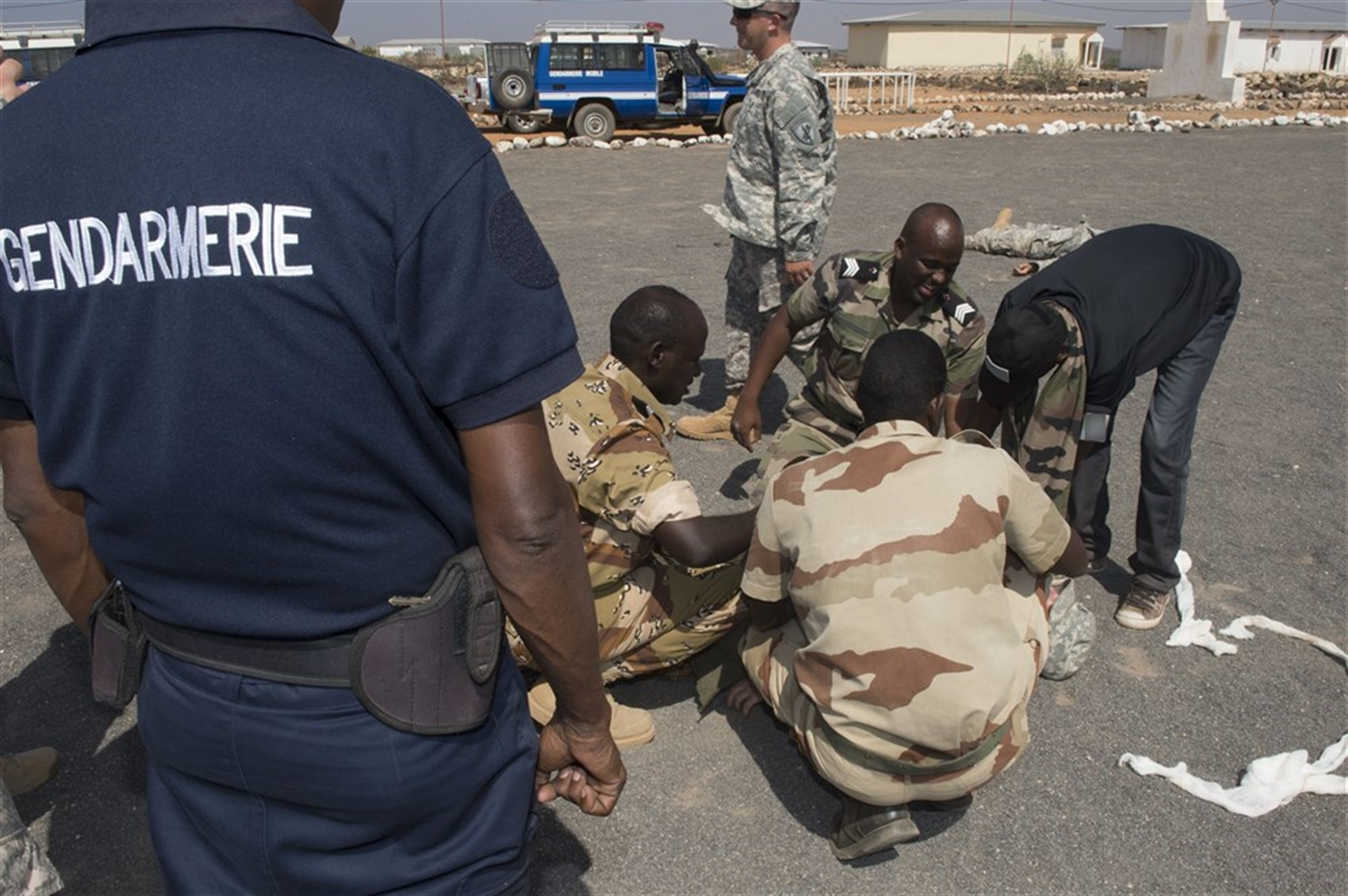 Captain Abdi Daher, Commander of Squadron 2 Gendarmerie Mobile (left) over watches his crew performing medical care during an mass casualty scenario during the First Aid Best Practice Exchange between, the Djibouti Gendarmerie, 404th and 407th Civil Affairs Battalions and the 1-77 Armored Regiment health care specialists in Cheik Moussa, Djibouti, Apr. 4, 2015. (U.S. Air Force Photos by Staff Sgt. Carlin Leslie)