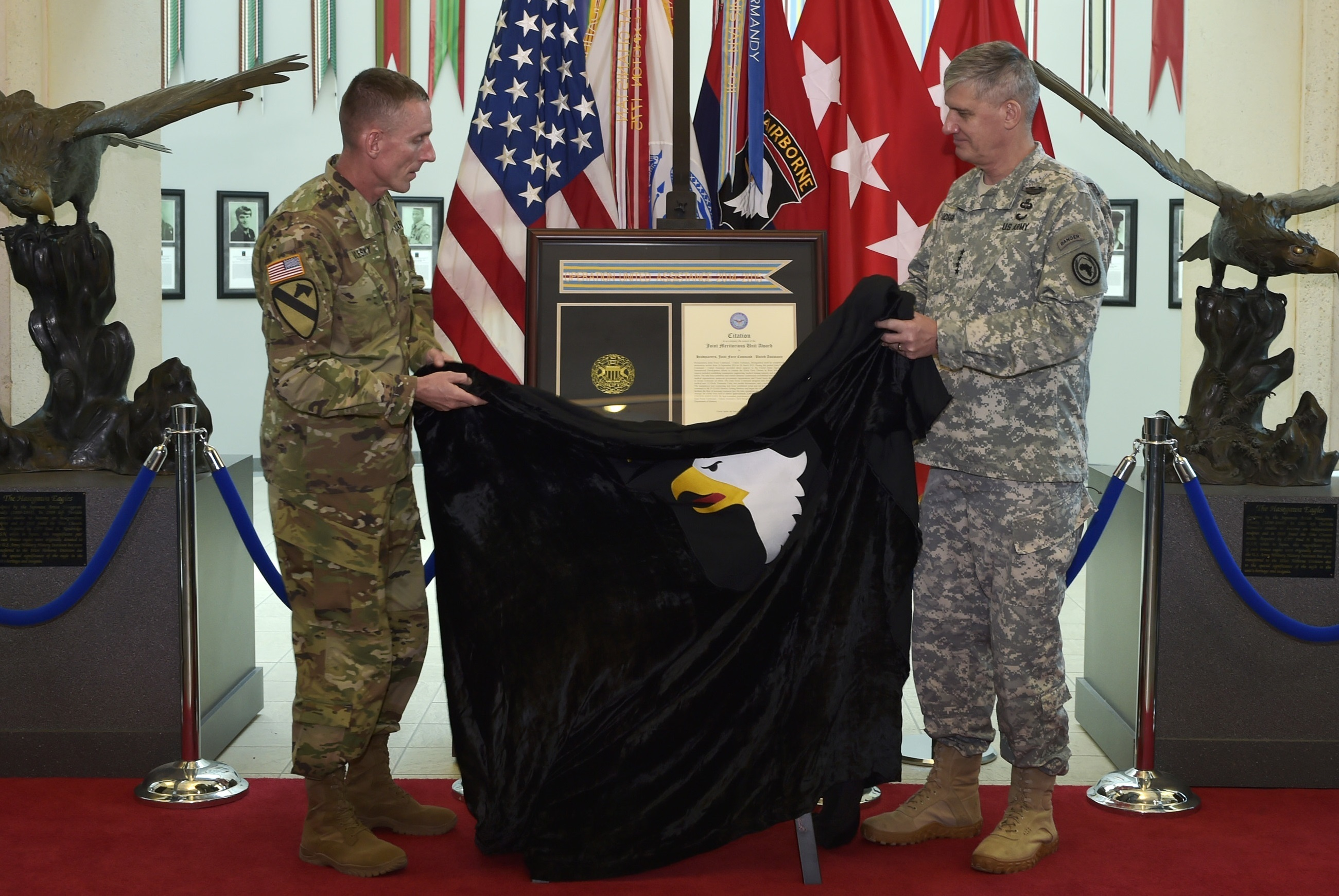 From right: Gen. David M. Rodriguez, commanding general, U.S. Africa Command, and Maj. Gen. Gary J. Volesky, commanding general, 101st Airborne Division (Air Assault) and Fort Campbell, unveil the Joint Meritorious Unit Award during a ceremony at McAuliffe Hall August 27, 2015. The JMUA, the second most prestigious award a unit can receive, was presented to the 101st Airborne Division for their humanitarian mission during the Ebola epidemic in Liberia. (U.S. Army photo by Jerry Woller, Lead VI Specialist-Fort Campbell)
