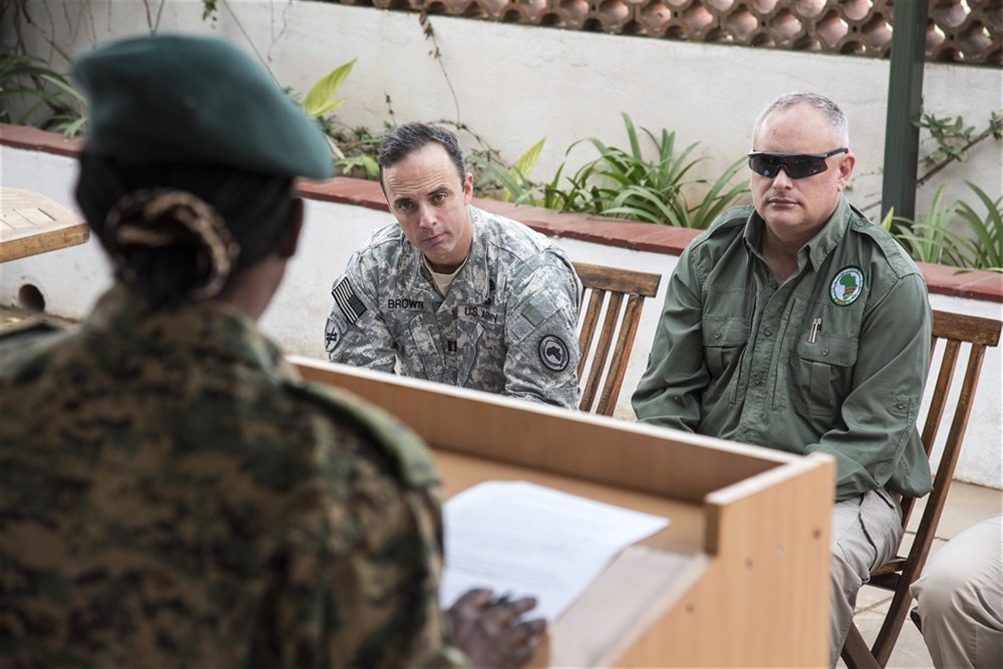 U.S. Army Capt. Daniel Brown, Africa Contingency Operations Training & Assistance (ACOTA) African Union Mission in Somalia (AMISOM) Force Headquarters training public affairs mentor, left, and Edward Wilson, ACOTA instructor, right, act as media during a mock press conference at the International Peace Support Training Center in Nairobi, Kenya, Aug. 25, 2015. The course was designed to prepare staff officers from AMISOM contributing countries for possible assignment to AMISOM Force Headquarters, and the public affairs mentors questioned AMISOM PA representatives to prepare them for the significant media presence in Somalia. (U.S. Air Force photo by Staff Sgt. Nathan Maysonet/released)