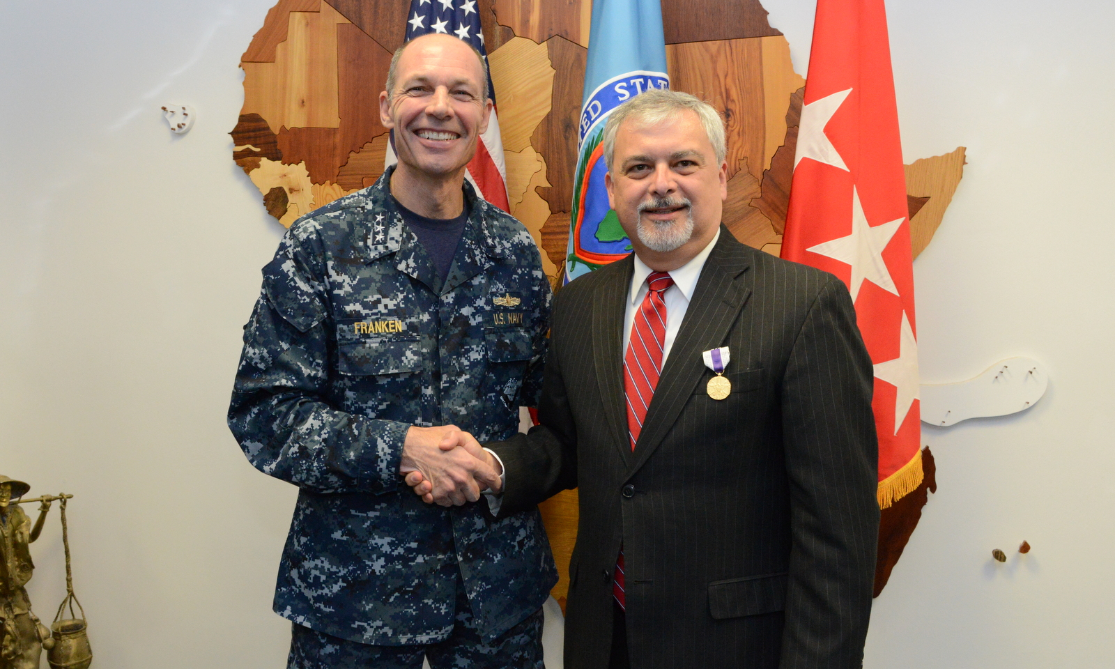 Ambassador Phillip Carter III, right, the outgoing deputy to the commander for civil military engagement with U.S. Africa Command, shakes hands with U.S. Navy Vice Adm. Michael T. Franken, the AFRICOM deputy to the commander for military operations, after Carter received the Joint Distinguished Civilian Service Award during a ceremony at Kelley Barracks, U.S. Army Garrison Stuttgart, Germany, Sept. 17, 2015. Carter served as the commander's senior diplomat and civilian advisor to the commander since November 2013.