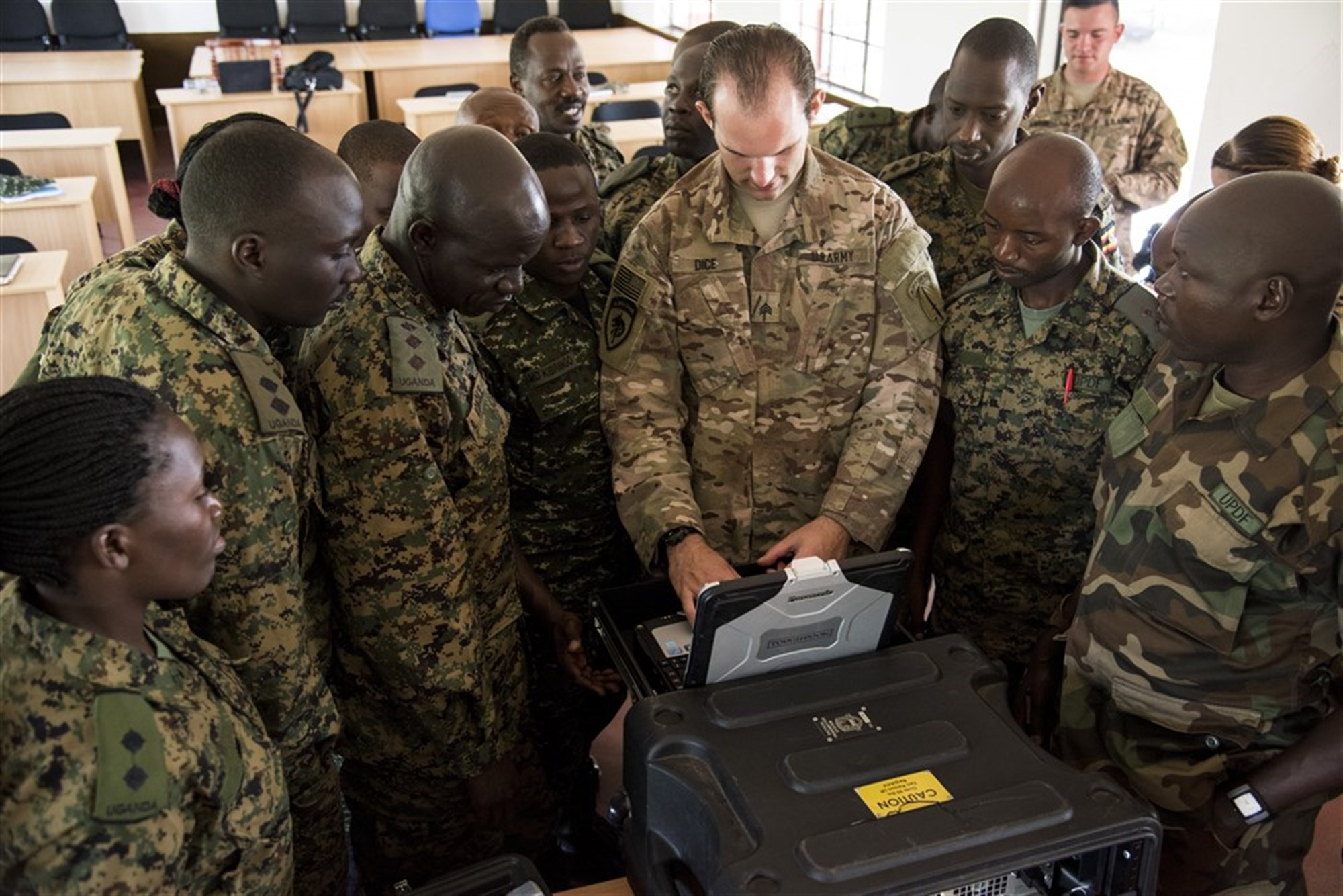 U.S. Army Sgt. Zechariah Dice, information operations course instructor, shows Uganda People's Defense Force (UPDF) personnel how to use a tactical transmitter system during an information operations course at Jinja, Uganda, recently. Its use was part of a course designed to help the UPDF develop their ability to plan and disseminate information to civilians and violent extremist organizations to inform and reduce the need for force. (U.S. Air Force photo by Staff Sgt. Nathan Maysonet)