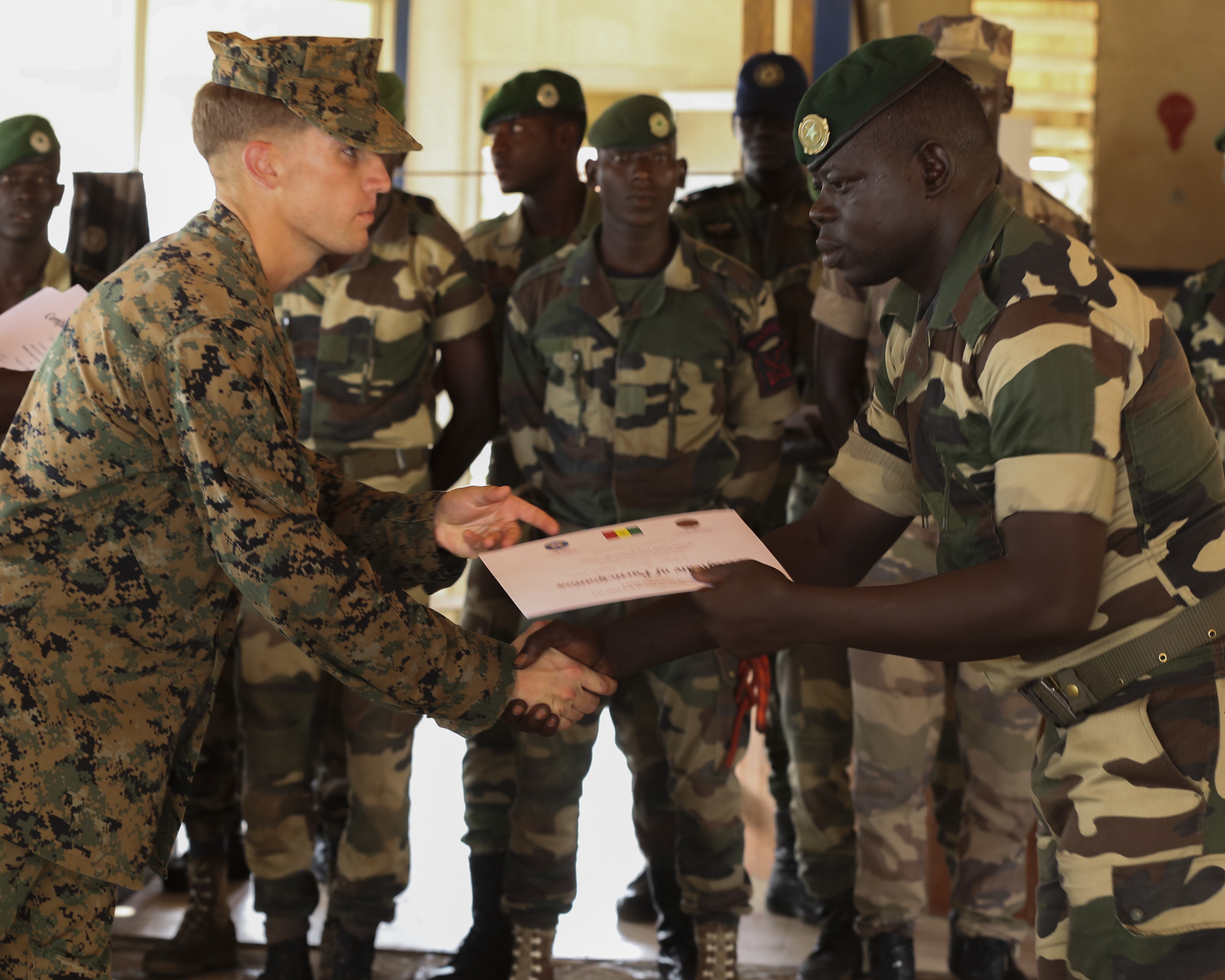 Second Lt. Aaron Burtner, security cooperation team leader, congratulates a Compagnie Fusilier de Marin Commando during his graduation ceremony after completing the final exercise with U.S. service members in Dakar, Senegal, September 17, 2015. The Marines and Coast Guardsmen with Special-Purpose Marine Air-Ground Task Force Crisis Response-Africa spent four weeks training the COFUMACO on basic infantry tactics and small-boat operations as a part of a Maritime Security Force Assistance mission to increase interoperability with Senegal's and strengthen the bond between the partner nations. (U.S. Marine Corps photo by Cpl. Olivia McDonald/Released)