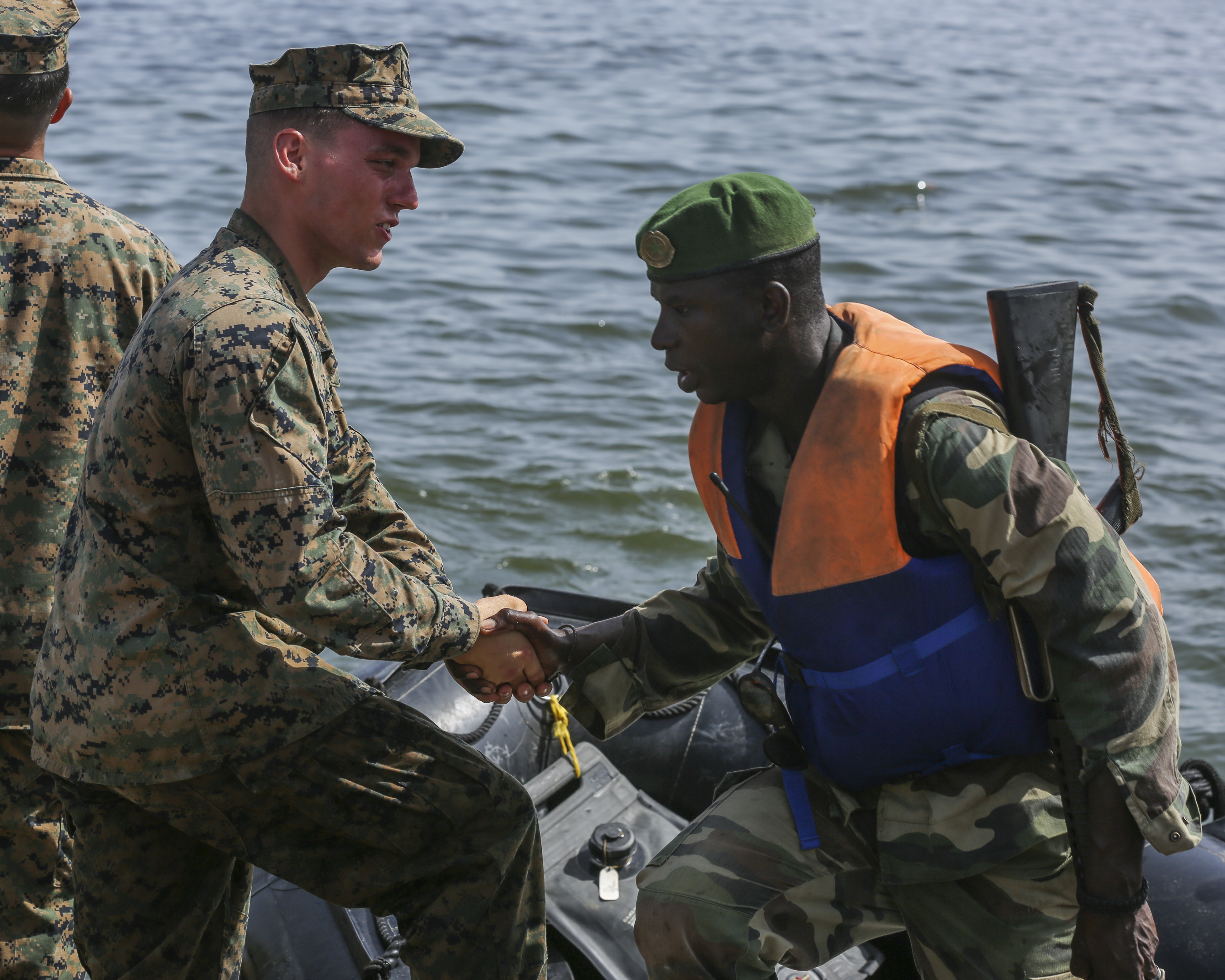 U.S. Marine Lance Cpl. Austin Carpenter, a rifleman, shakes his counterpart Compagnie Fusilier de Marin Commando's hand after successfully completing the final exercise with U.S. service members in Dakar, Senegal, Sept. 17, 2015. The Marines and Coast Guardsmen with Special-Purpose Marine Air-Ground Task Force Crisis Response-Africa spent four weeks training the COFUMACO on basic infantry tactics and small-boat operations as a part of a Maritime Security Force Assistance mission to increase interoperability with Senegal's and strengthen the bond between the partner nations. (U.S. Marine Corps photo by Cpl. Olivia McDonald/Released)