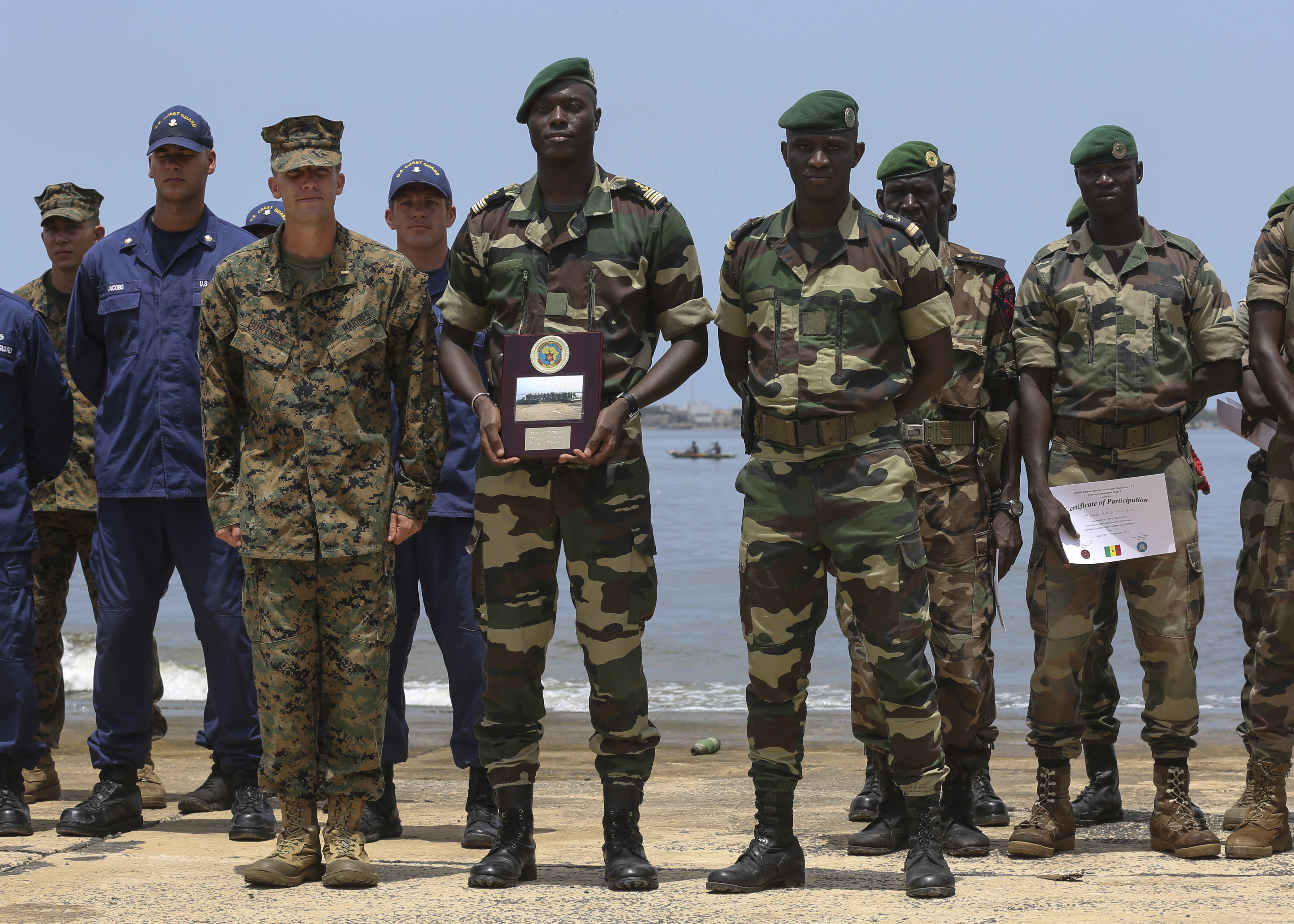 Second Lt. Aaron Burtner, security cooperation team leader, poses for a photo with Compagnie Fusilier de Marin Commandos after completing their final exercise with U.S. service members in Dakar, Senegal, September 17, 2015. The Marines and Coast Guardsmen with Special-Purpose Marine Air-Ground Task Force Crisis Response-Africa spent four weeks training the COFUMACO on basic infantry tactics and small-boat operations as a part of a Maritime Security Force Assistance mission to increase interoperability with Senegal's and strengthen the bond between the partner nations.  (U.S. Marine Corps photo by Cpl. Olivia McDonald/Released)
