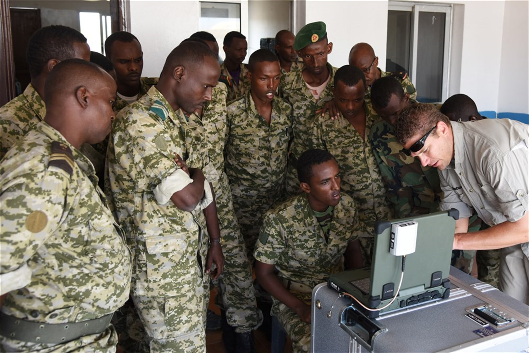 Joseph Brunette, iRobot instructor, shows Djibouti Armed Forces (FAD) service members how to use a computer to monitor what the 510 Packbot is searching. The robot searches for, and dispose of, explosive weapons.