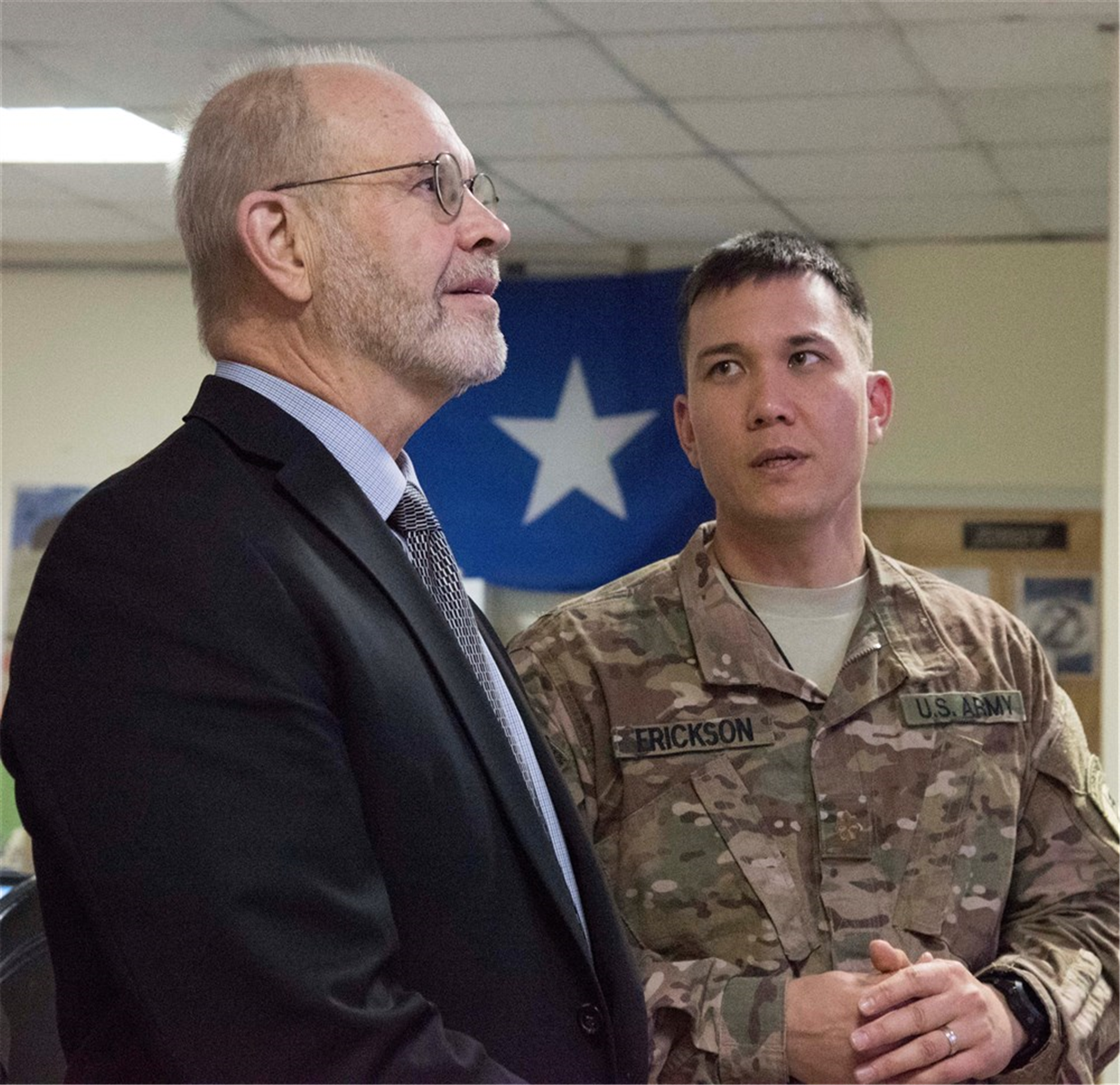 Retired Ambassador David Kaeuper, U.S. Chargé d'Affaires to Somalia hears an explanation from U.S. Army Maj. Kristopher Erickson, Somalia desk lead for the Fusion Action Cell hive at Camp Lemonnier, Djibouti, Oct. 15, 2015. The FAC personnel are separated into country desks composed of subject matter experts and foreign liaison officers who are responsible for streamlining the planning and coordination of projects in their respective countries. (U.S. Air Force photo by Staff Sgt. Victoria Sneed/Released)