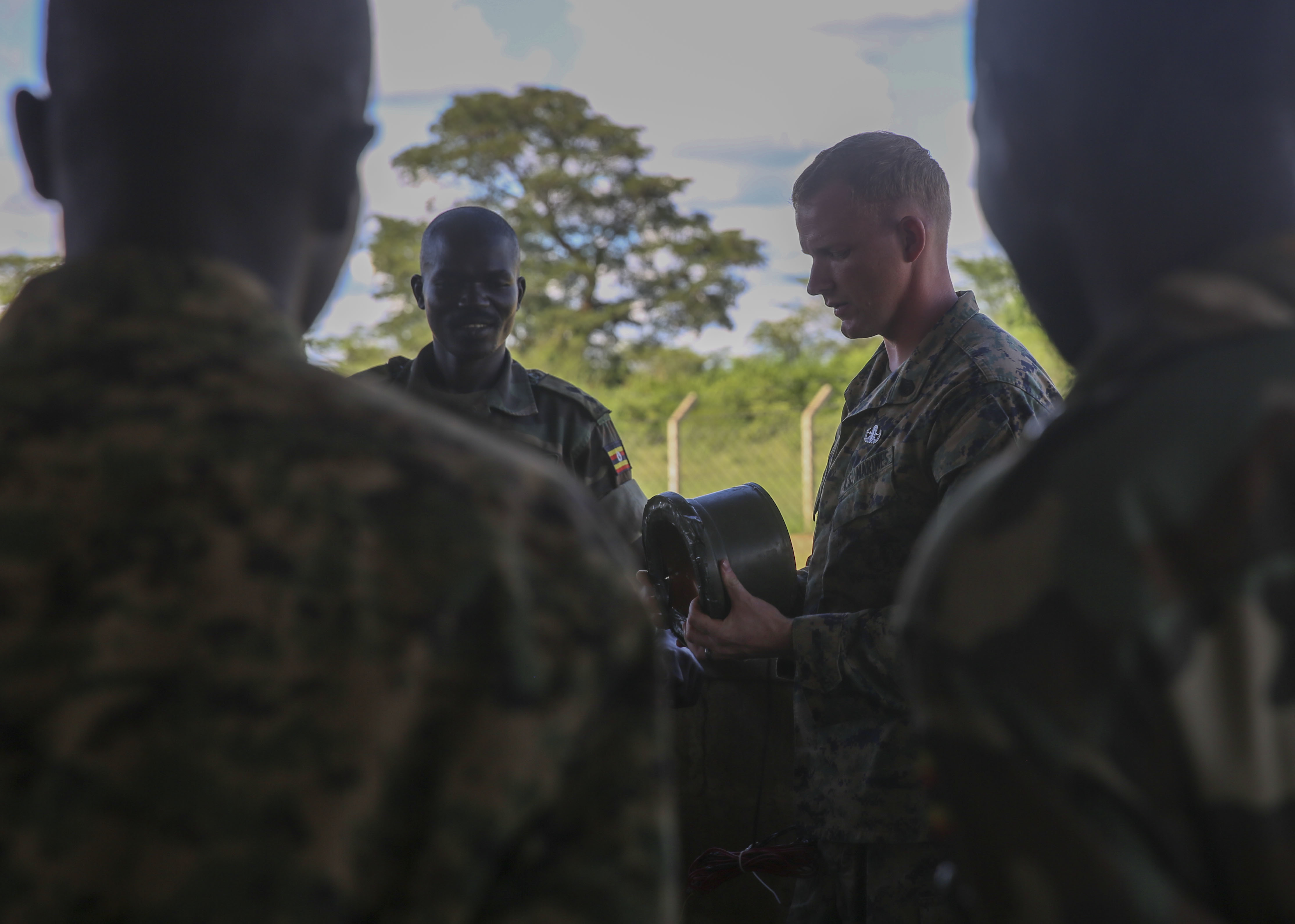 U.S. Marine Staff Sgt. Malachi McPherson, an explosive ordnance disposal technician with Special-Purpose Marine Air-Ground Task Force Crisis Response-Africa, shows some of the different types of improvised explosive devices to members of the Uganda People's Defense Force during an IED awareness class at Camp Singo, Uganda, Nov. 2, 2015. Marines and sailors with SPMAGTF-CR-AF are training with the UPDF to increase engineering and logistical capabilities while strengthening the bonds between the partner counties. (U.S. Marine Corps photo by Cpl. Olivia McDonald/Released)