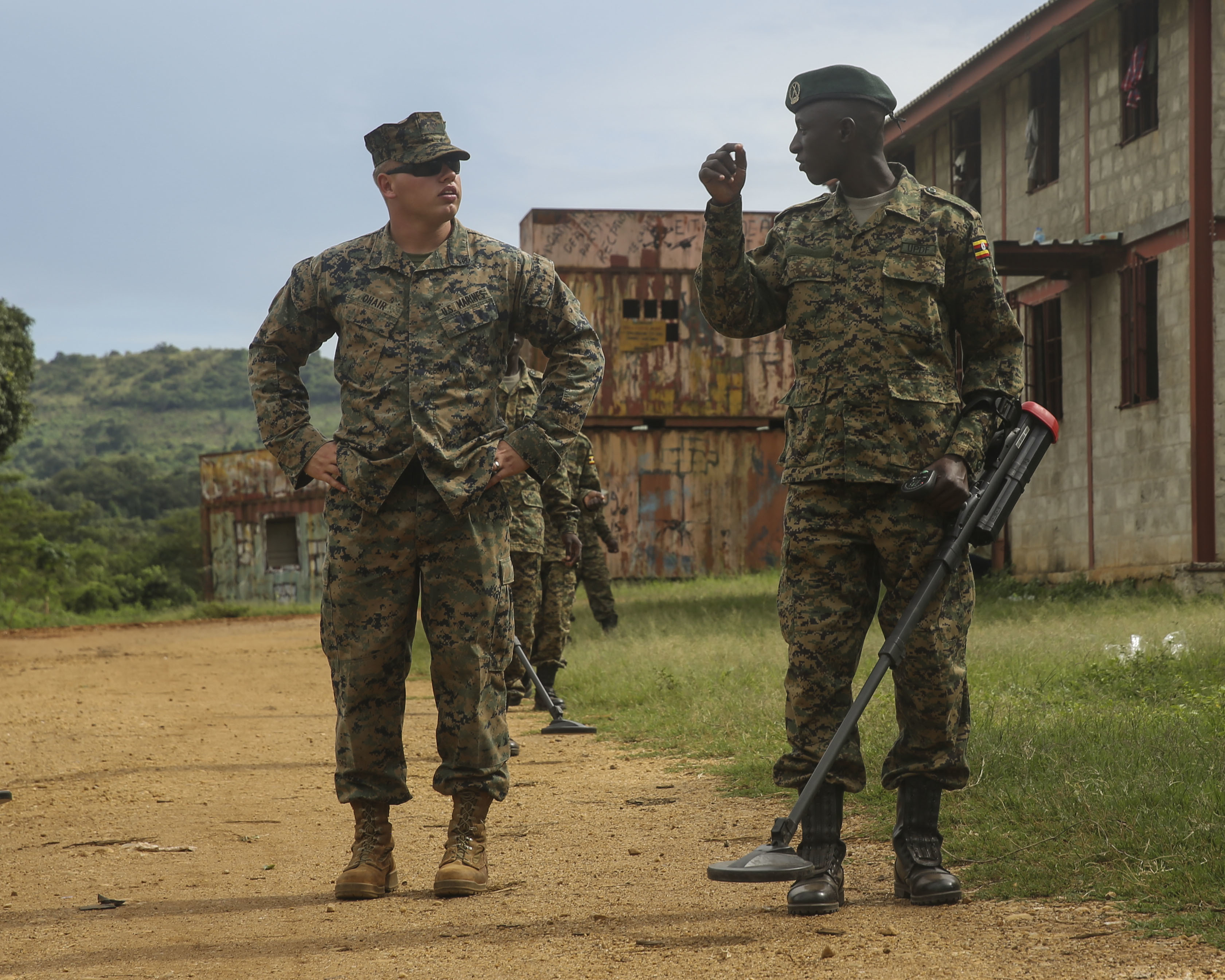 U.S. Marine Sgt. Sean O'Hair, a combat engineer with Special-Purpose Marine Air-Ground Task Force Crisis Response-Africa, helps a member of the Uganda People's Defense Force through an improvised explosive device awareness exercise at Camp Singo, Uganda, Nov. 3, 2015. Marines and sailors with SPMAGTF-CR-AF are training with the UPDF to increase engineering and logistical capabilities while strengthening the bonds between the partner counties. (U.S. Marine Corps photo by Cpl. Olivia McDonald/Released)