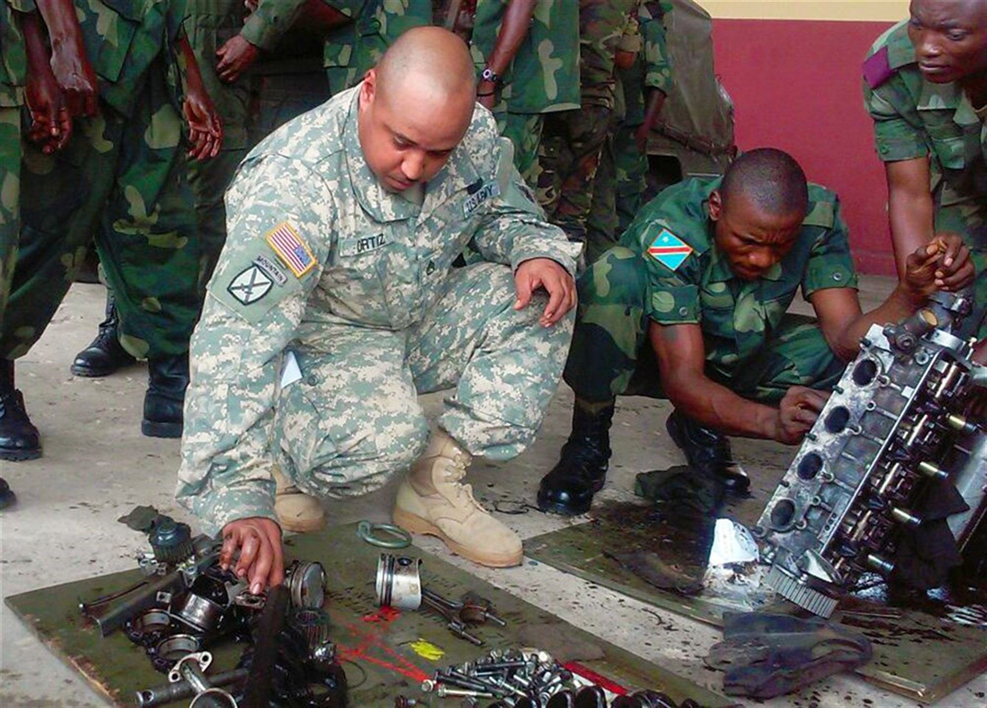 U.S. Army Africa's role in supporting training through the Democratic Republic of Congo's Defense Logistics School is an example of how AFRICOM can increase the capacity of partner nations to provide logistics support to their own forces. Here, Staff Sgt. Roberto Ortiz, a wheeled vehicle mechanic from AFRICOM's Regionally Aligned Force, 3rd Brigade, 1st Armored Division from Fort Bliss, Texas, provides assistance to a DRC student rebuilding a light truck engine during hands on training at the DRC Logistics School. (U.S. Army Africa photo)