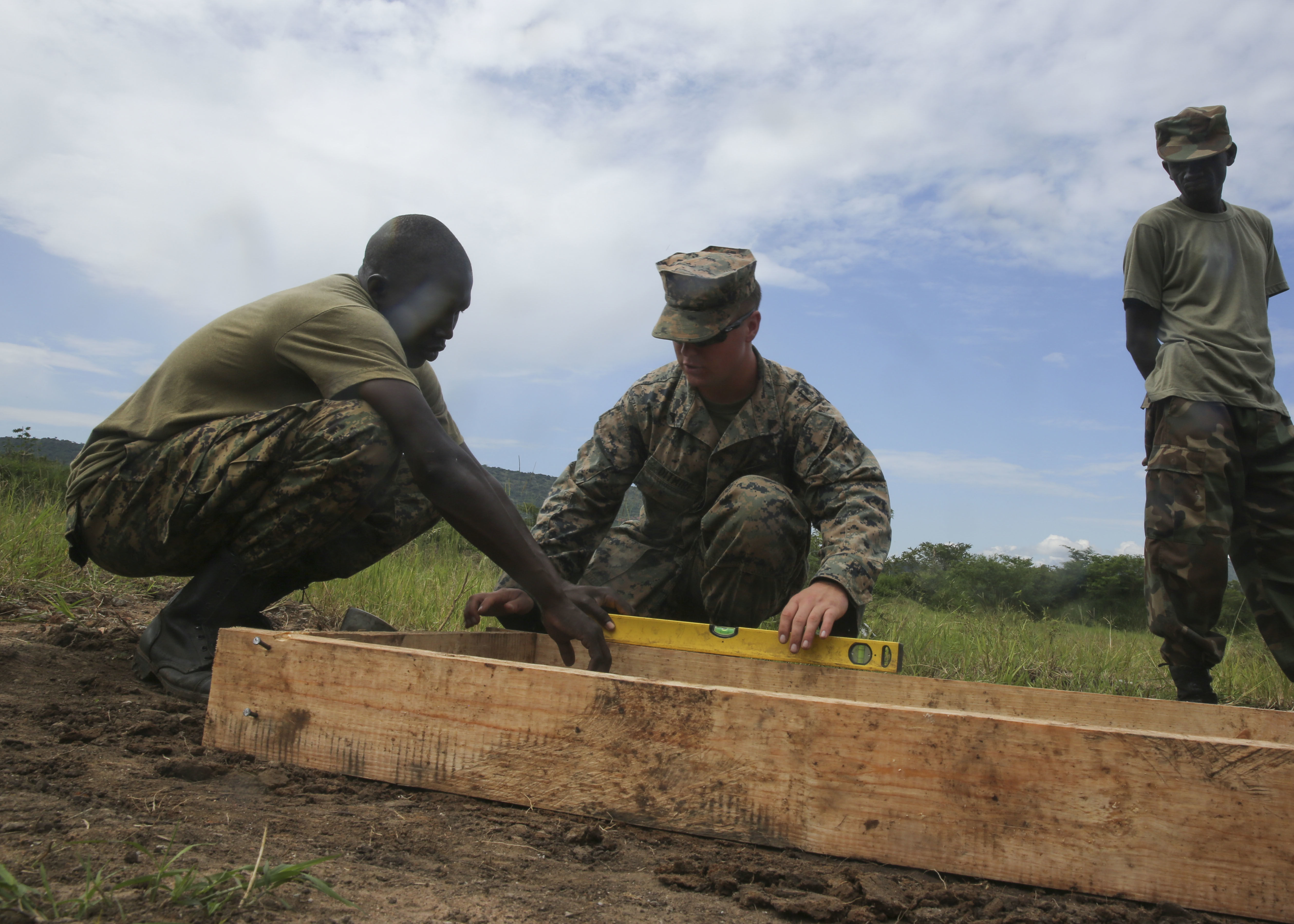 U.S. Marine Cpl. Brandon Ditmire, a combat engineer with Special-Purpose Marine Air-Ground Task Force Crisis Response-Africa, assists a Uganda People's Defense Force soldier level the base for a concrete slab during a civil engineering exercise at Camp Singo, Nov. 16, 2015. The exercise helps the partner nations fortify their civil engineering skills while strengthening the bond between the two. (U.S. Marine Corps photo by Cpl. Olivia McDonald/Released)