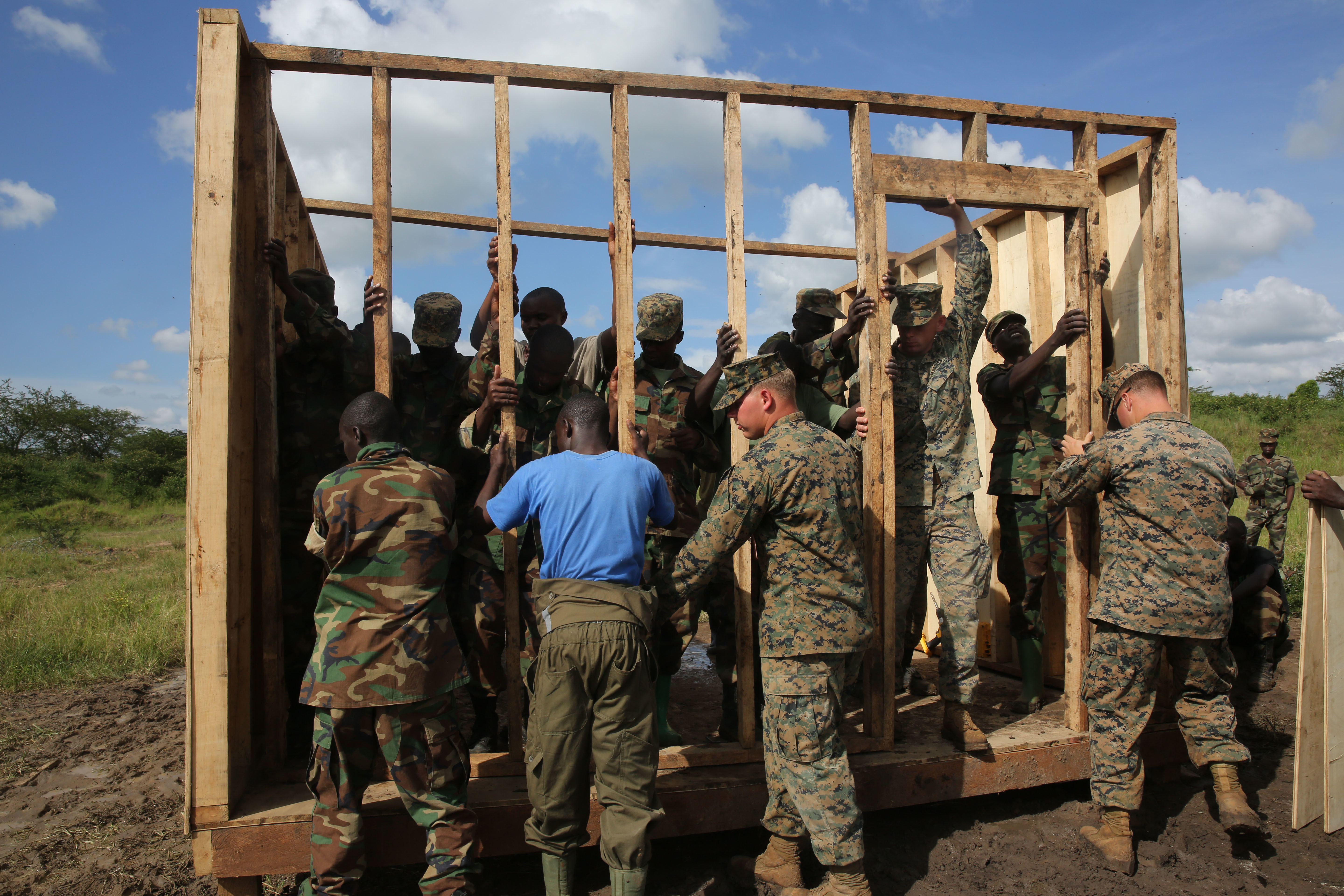 U.S. Marine combat engineers with Special-Purpose Marine Air-Ground Task Force Crisis Response-Africa, assist Uganda People's Defense Force soldiers nail in one of the wall frames during a civil engineering exercise at Camp Singo, Nov. 19, 2015. The exercise helps the partner nations fortify their civil engineering skills while strengthening the bond between the two. (U.S. Marine Corps photo by Cpl. Olivia McDonald/Released)