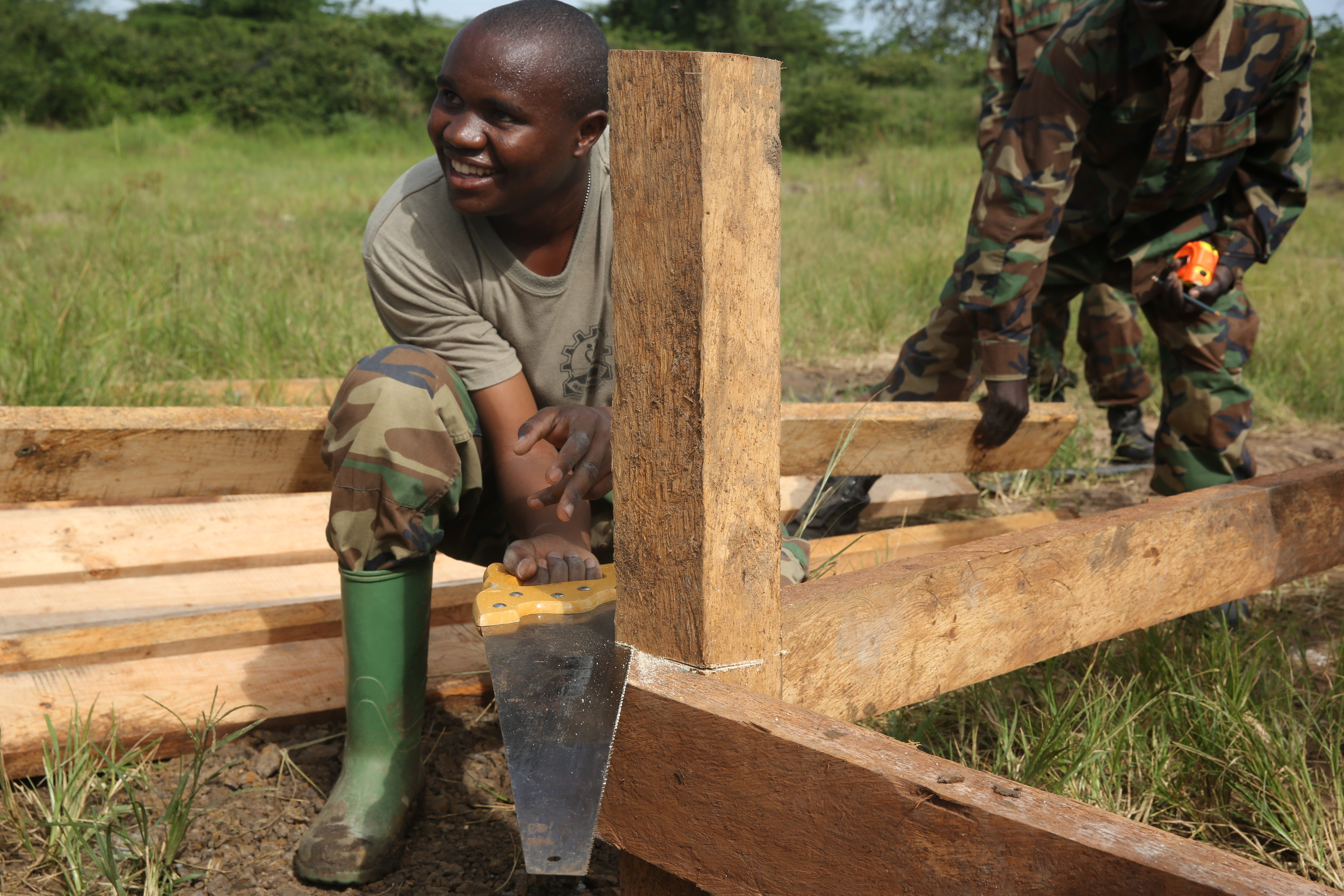 A Uganda People's Defense Force soldier saws the top of a post in preparation to finish the flooring during a civil engineering exercise at Camp Singo, Nov. 16, 2015. The exercise helps the partner nations fortify their civil engineering skills while strengthening the bond between the two. (U.S. Marine Corps photo by Cpl. Olivia McDonald/Released)