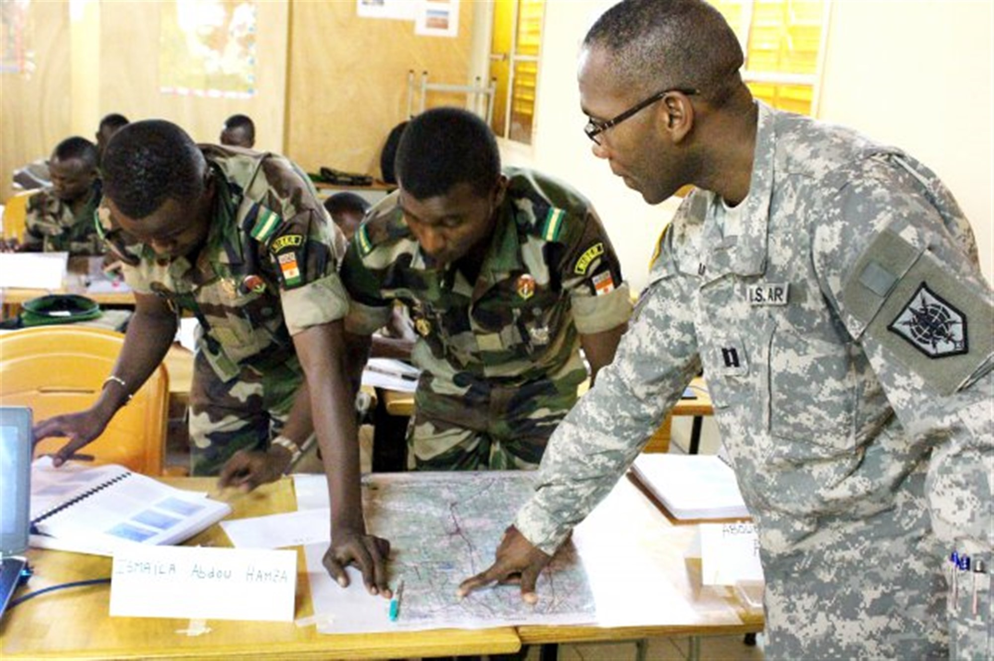 Nigerien Army Lieutenants Ismaila Abdou Hamza and Aboubacar Anadon and U.S. Army Capt. Dominique Louis plot targets for analysis during their basic map-reading course in Niamey, Niger, Oct. 28, 2015.