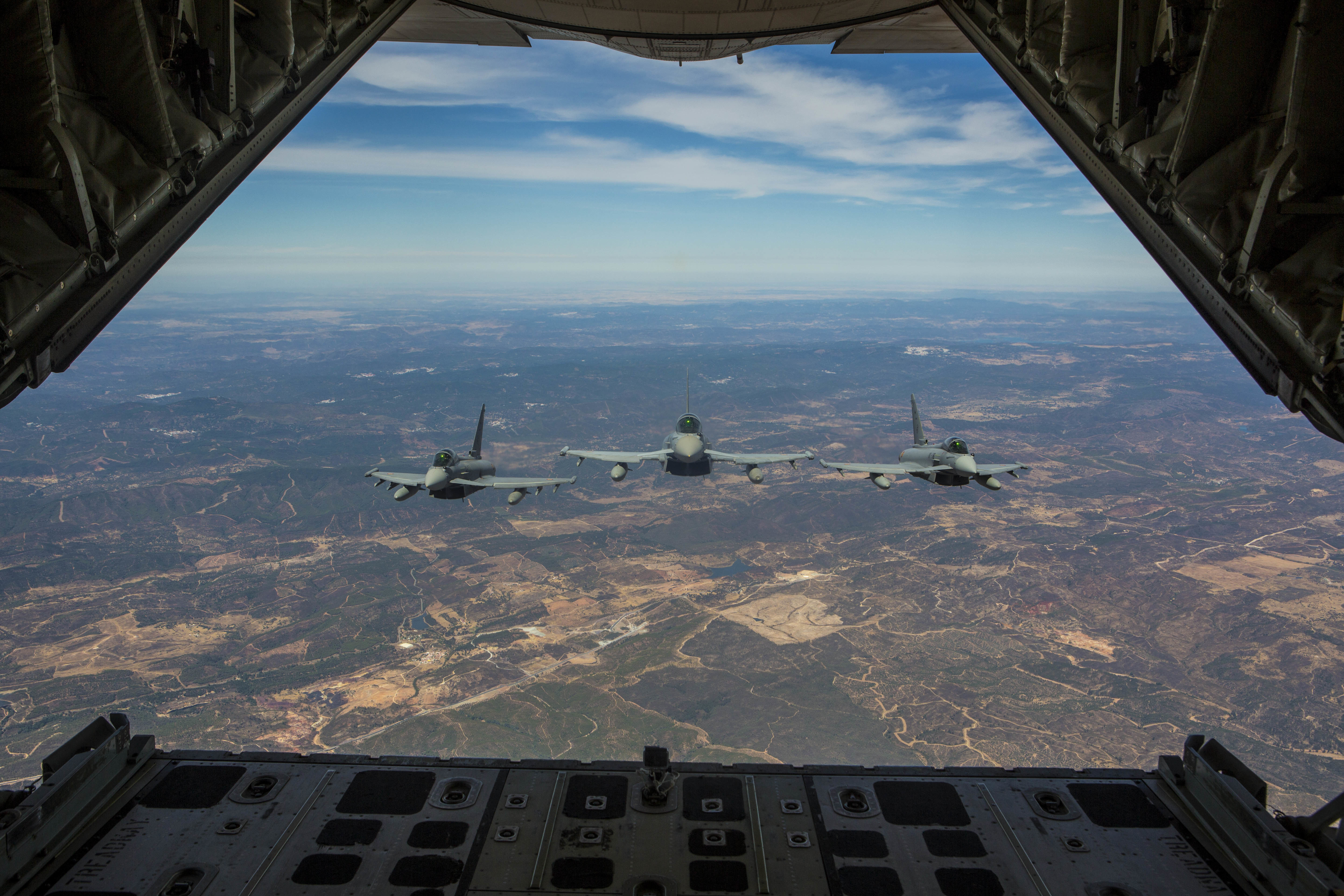 Three Eurofighter Typhoons with the Spanish Air Force escort a U.S. Marine Corps KC-130J Hercules during an aerial refueling mission, Aug. 13, in Spain. Bilateral exercises such as this one are how Spain and the U.S. foster one of the closest defense partnerships around the world. (U.S. Marine Corps photo by Staff Sgt. Vitaliy Rusavskiy/Released)