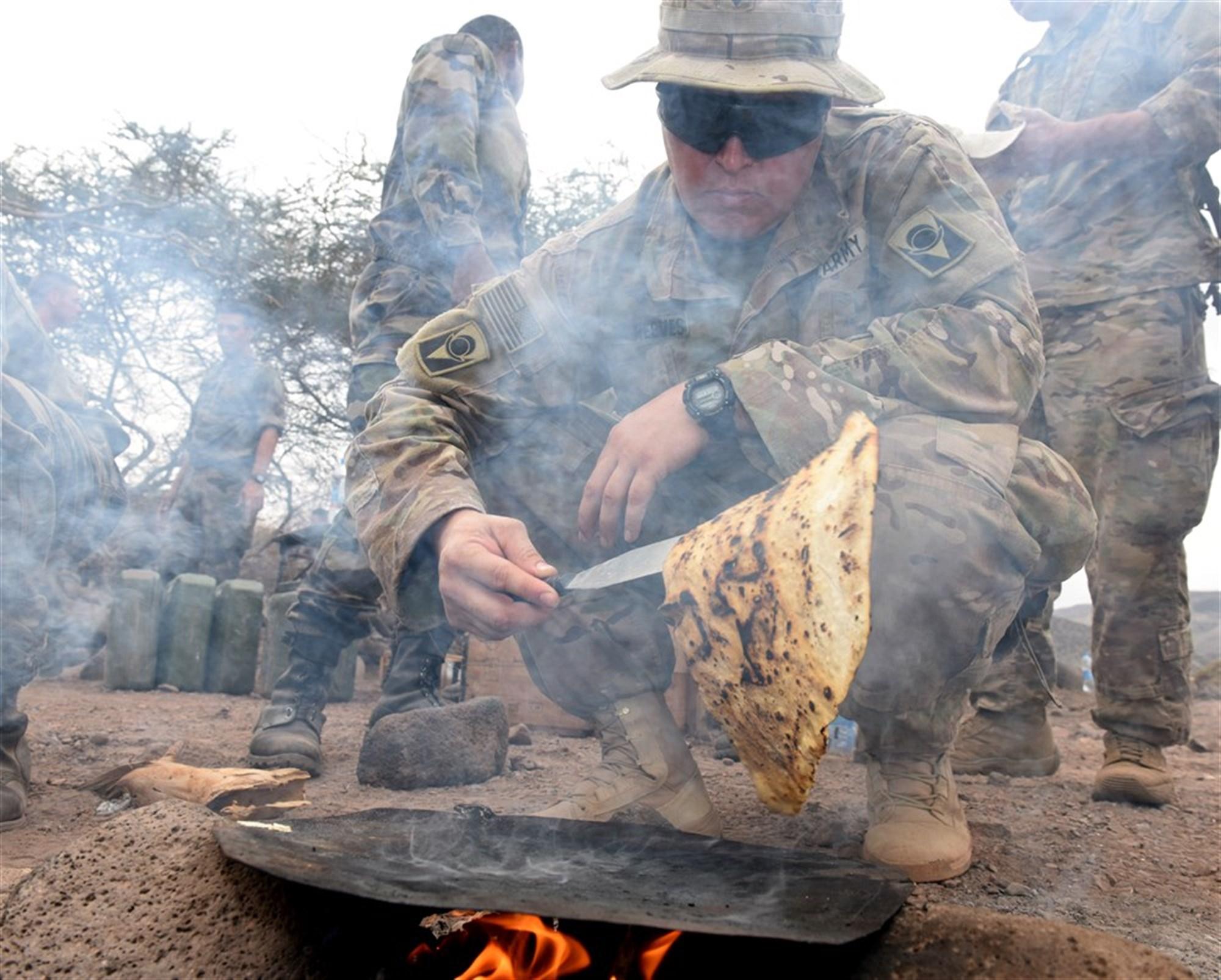 U.S. Army Spc. Christopher Reeves, 2-124 Infantry Battalion mechanic,  grills flatbread