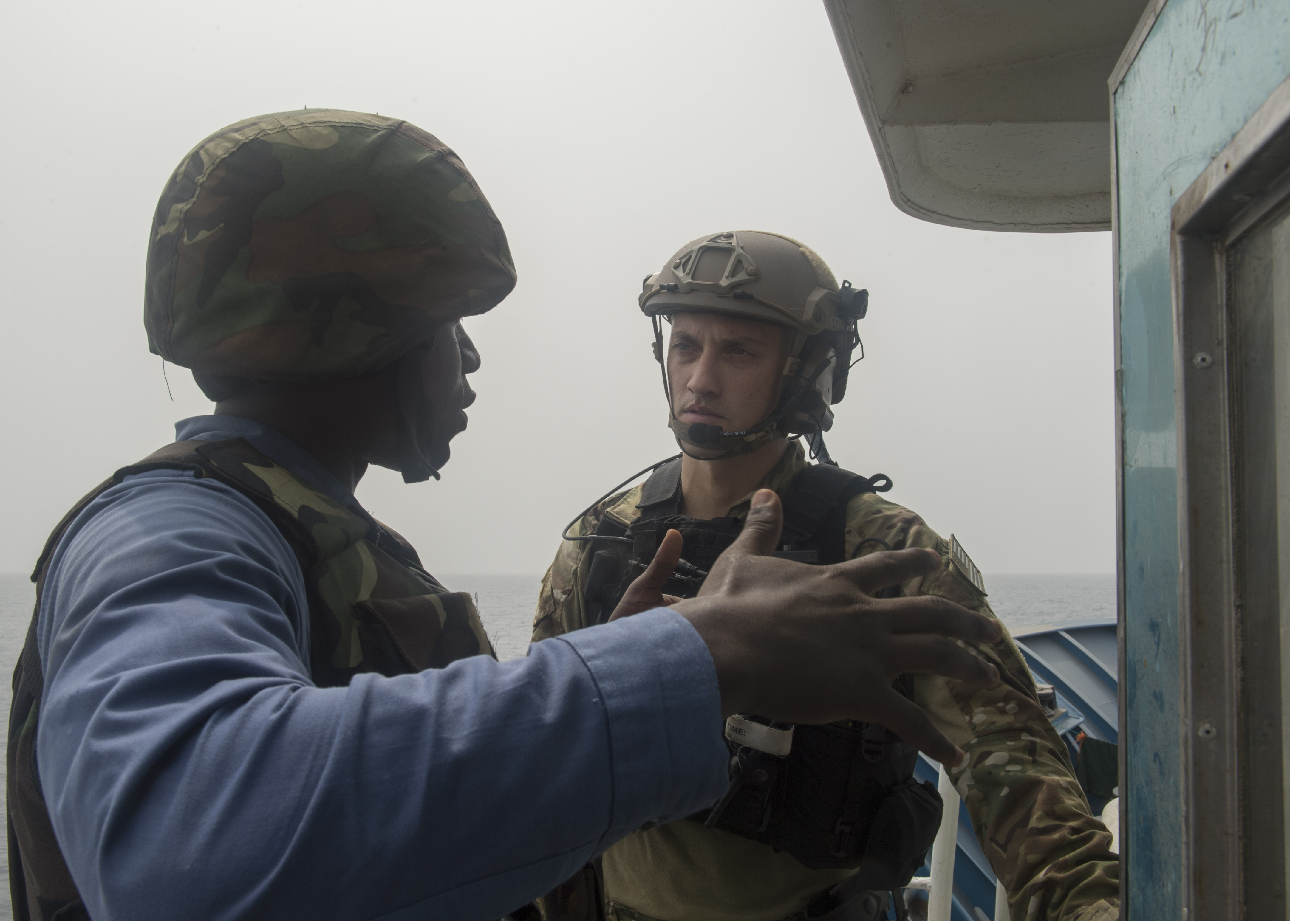 160204-N-WV703-025 ATLANTIC OCEAN (Feb. 04, 2016) A member of the Ghanaian Navy and a U.S. Coast Guard Tactical Law Enforcement Detachment member discuss boarding procedure while on a fishing vessel that was boarded during combined joint boarding operations Feb. 04, 2016. The Military Sealift Command expeditionary fast transport vessel USNS Spearhead (T-EPF 1) is on a scheduled deployment in the U.S. 6th Fleet area of operations to support the international collaborative capacity-building program Africa Partnership Station. (U.S. Navy photo by Mass Communication Specialist 3rd Class Amy M. Ressler/Released)