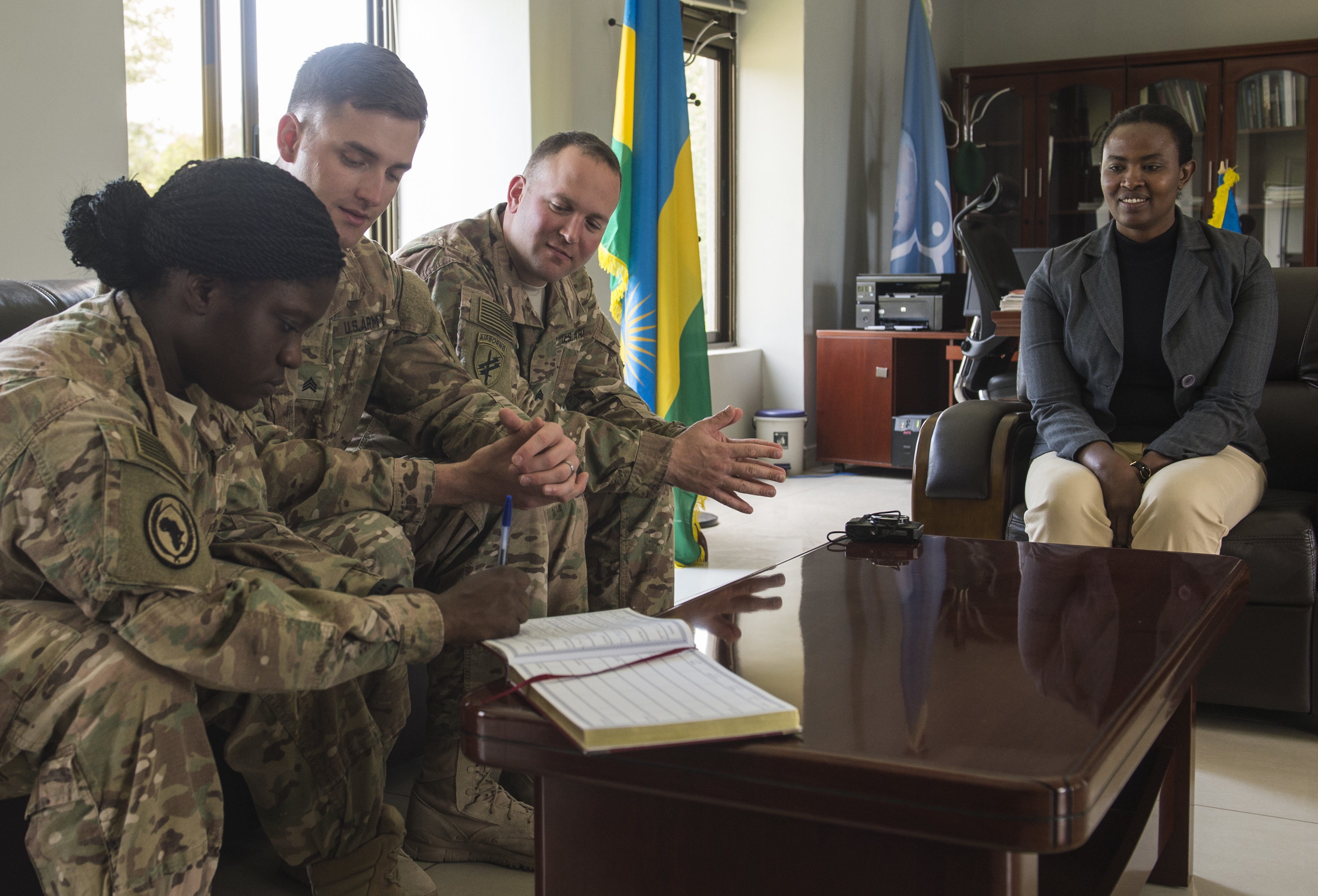 Representatives from the Combined Joint Task Force-Horn of Africa Army civil affairs battalion and information operations office sign a guest book at the Rwanda Peace Academy Feb. 4, 2016, in Musanze, Rwanda. Rwanda is one of the largest contributors of forces to peacekeeping operations in East Africa. The Ministry of Defence's impact continues to expand as the Rwanda Peace Academy takes on a larger role as an international training, research and education center. (U.S. Air Force photo by Senior Airman Peter Thompson)