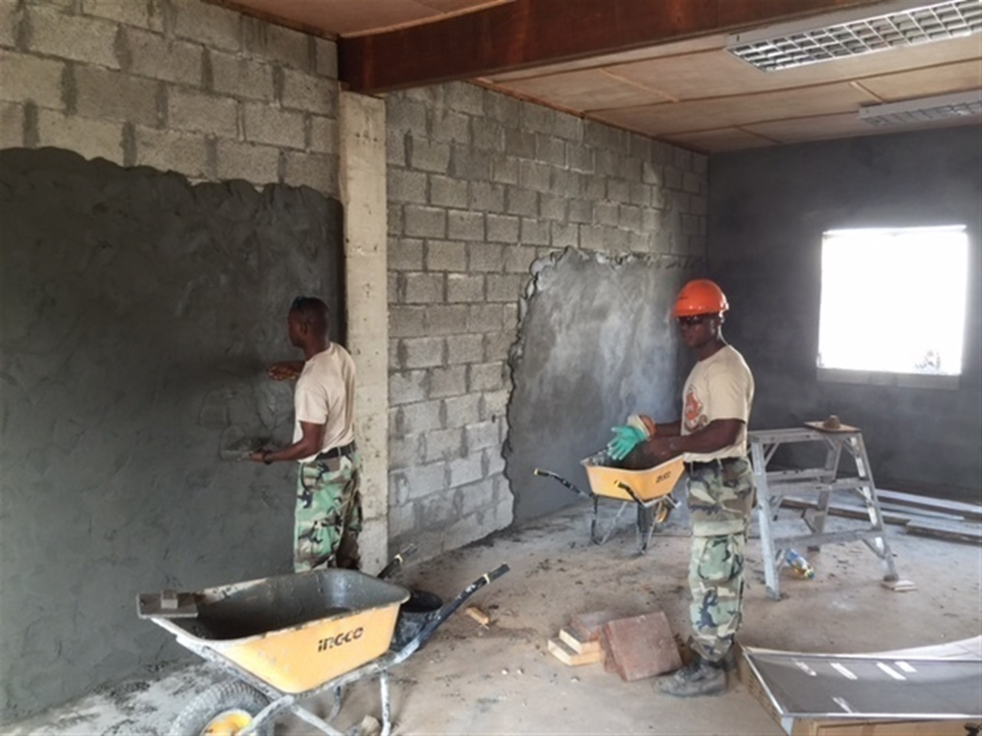 MONROVIA, Liberia - Armed Forces of Liberia Soldiers apply a cement-like mud to the interior walls of two new multipurpose buildings, Feb. 3, 2016, at the Edward Binyah Kesselly military training facility in Monrovia, Liberia. The buildings were constructed in partnership with Michigan Army National engineers during four Security Cooperation Opportunity Unit Training rotations. Maj. Gen. Gregory Vadnais, adjutant general of the Michigan National Guard, traveled to Liberia to cut the ribbon on the buildings and celebrate Liberian Armed Forces Day, Feb. 10, 2016, with the last SCOUT rotation, the MIARNG 1434th Engineer Company, AFL leaders and Liberian President Ellen Johnson Sirleaf. (U.S. Army National Guard photo by Maj. David Huber/Released)