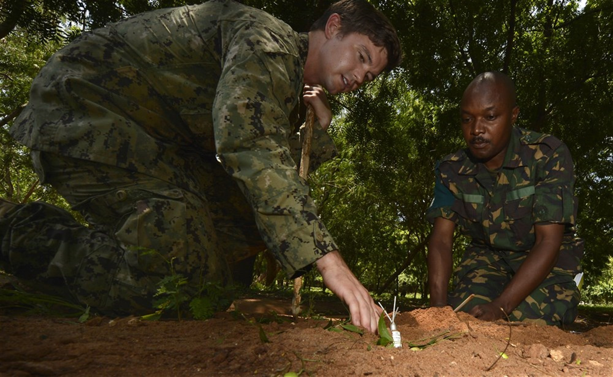 Explosive Ordnance Disposal Technician 3rd Class Andrews, EOD Mobile Unit 1, shows a member of the Tanzania People's Defence Force how to safely remove simulated unexploded landmines during the practical exercise portion of Humanitarian Mine Action Level 1 training in Dar es Salaam, Tanzania, Feb. 17, 2016. HMA activities include classroom instruction and practical exercises on detecting and clearing landmines, identifying and disposing of explosive remnants, and providing physical security and stockpile management.  (U.S. Air Force photo by Tech. Sgt. Dan DeCook)