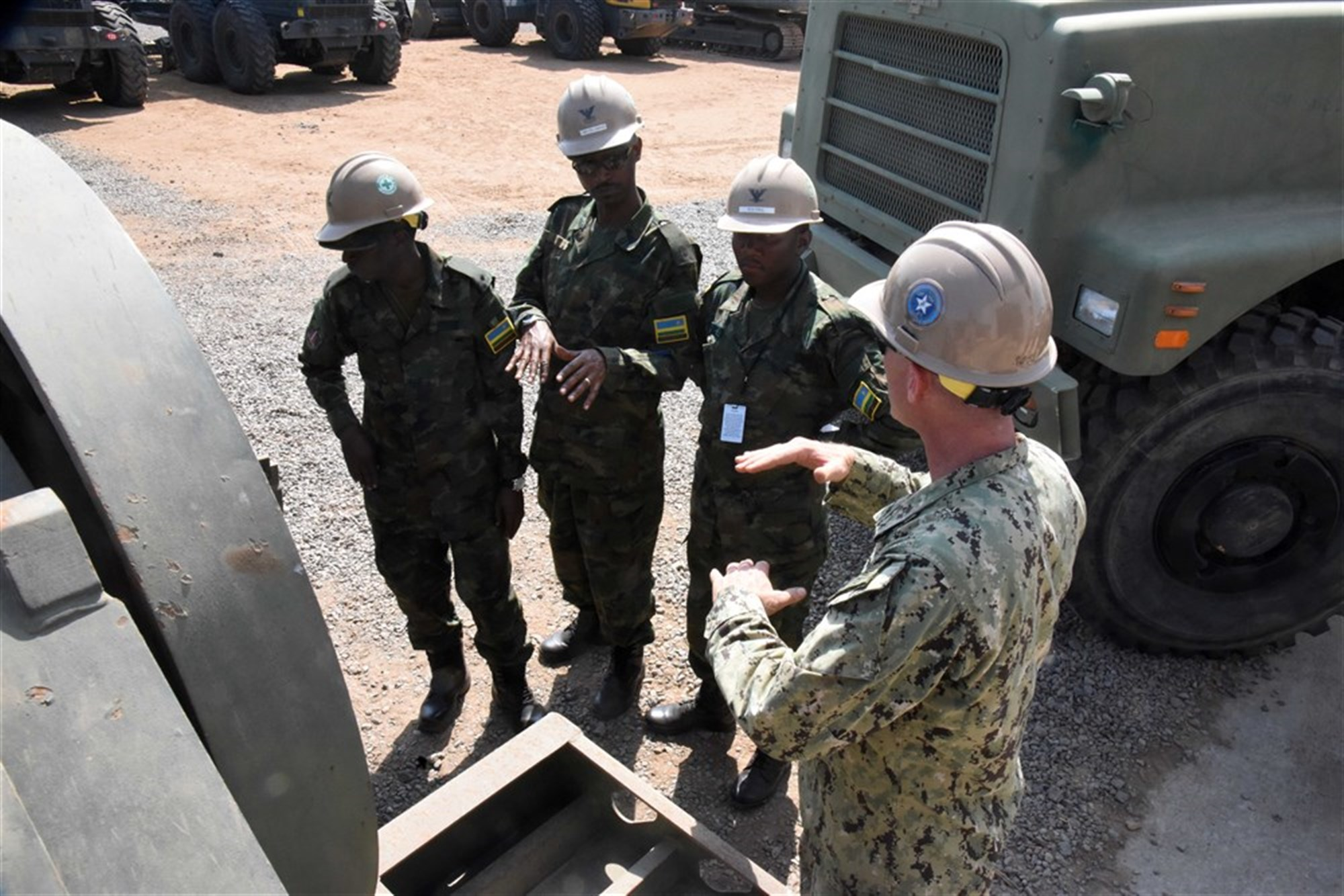 U.S. Navy Equipment Operator 2nd Class Tom Ross, Naval Mobile Construction Battalion 22, explains trailer detachment to Rwanda Defence Force engineers during their tour of Camp Lemonnier, Djibouti, Feb. 24, 2016. RDF members learned more about U.S. expeditionary camps and what equipment is used to build and maintain them. (U.S. Air Force photo by Staff Sgt. Victoria Sneed)