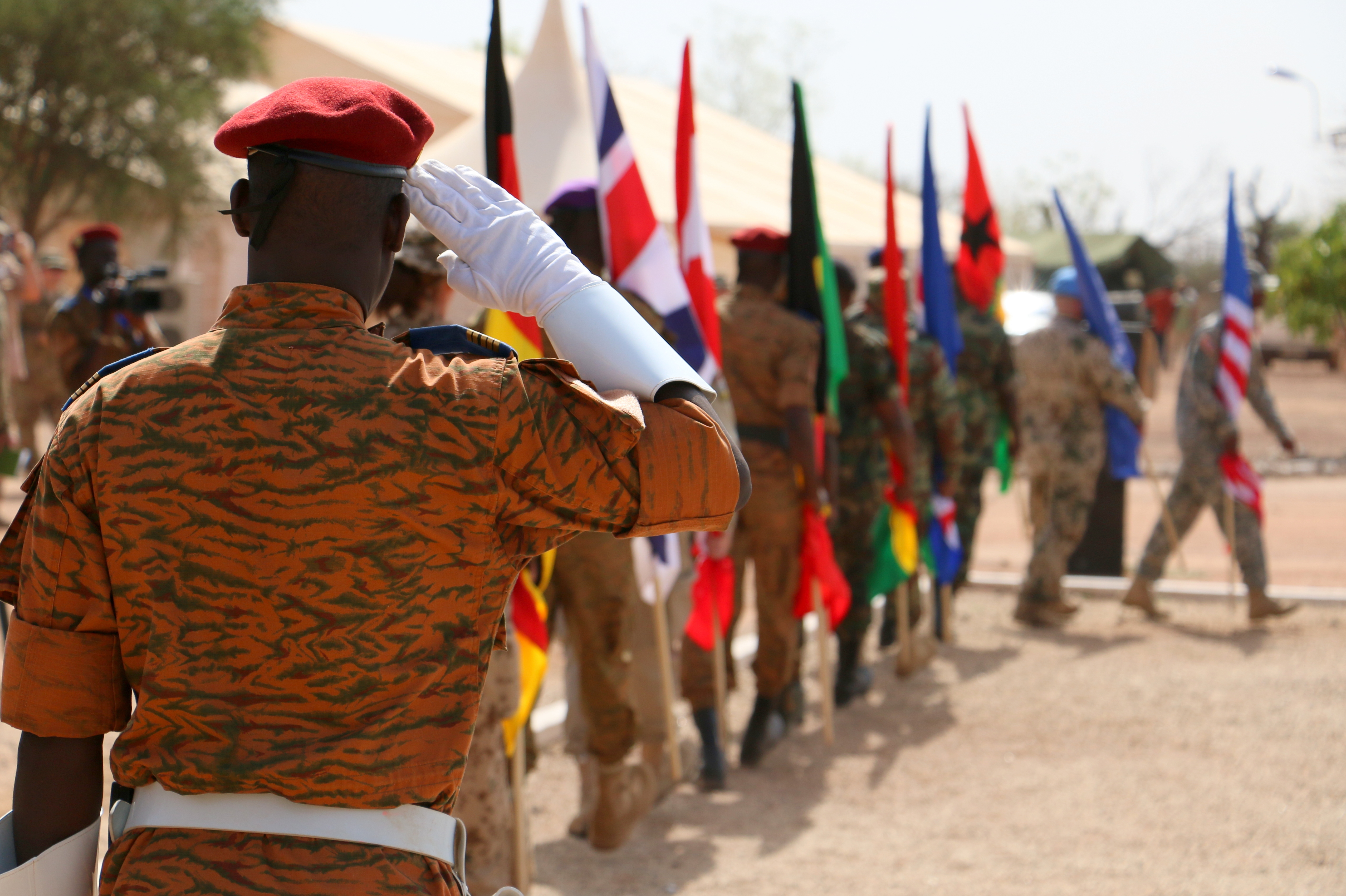 An officer from the Burkina Faso army salutes as international flags march past him during the Western Accord 16 Opening Day Ceremony May 2, 2016 at Camp Zagre, Ouagadougou, Burkina Faso. Western Accord 16 is an annual combined, joint exercise designed to increase the ability of African partner forces and the U.S. to exercise participants' capability and capacity to conduct African Union/United Nation mandated Peace Operations. (U.S. Army photo by Staff Sgt. Candace Mundt/Released)