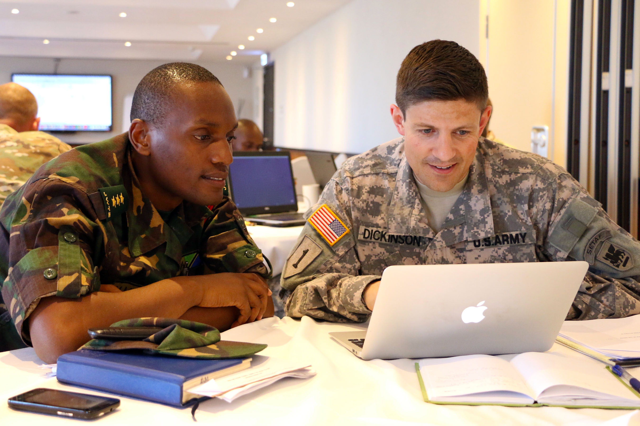 Capt. Joshua Dickinson, operational law attorney with U.S. Army Africa and Tanzanian People's Defense Force attorney Capt. Mbwambo discuss work on the exercise support agreement during the final planning event for exercise Eastern Accord 2016 in Dar es Salaam, Tanzania, May 2. EA 2016 is an annual, combined, joint military exercise bringing together partner nations to practice and demonstrate proficiency in conducting peacekeeping operations. (U.S. Army Africa photo by Capt. Jarrod Morris)