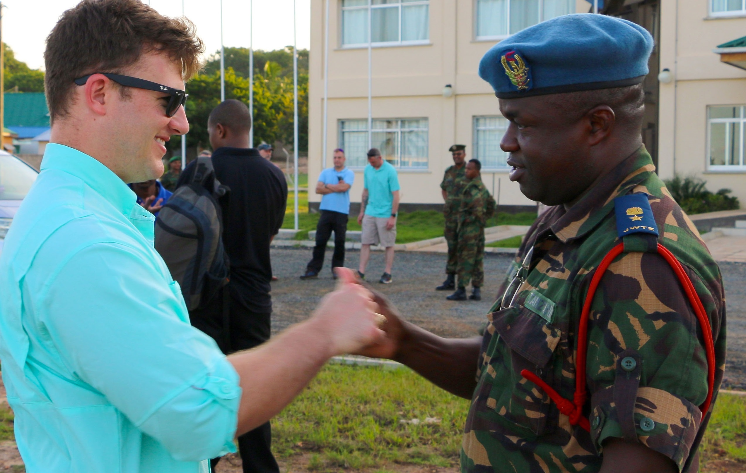 Tanzanian People's Defense Force Lt. Col. Hozza teaches a popular Tanzanian handshake to Capt. Bryan Neal, operations planner for 1st Battalion, 9th Field Artillery Regiment, 2nd Brigade Combat Team, 3rd Infantry Division, during the exercise Eastern Accord 2016 final planning event site visit to the Tanzanian Peacekeeping Training Center in Dar es Salaam, Tanzania, May 3. Soldiers of 1-9 FA are supporting EA 2016 this summer as part of the regionally allocated force for U.S. Army Africa and U.S. Africa Command. (U.S. Army Africa photo by Capt. Jarrod Morris)