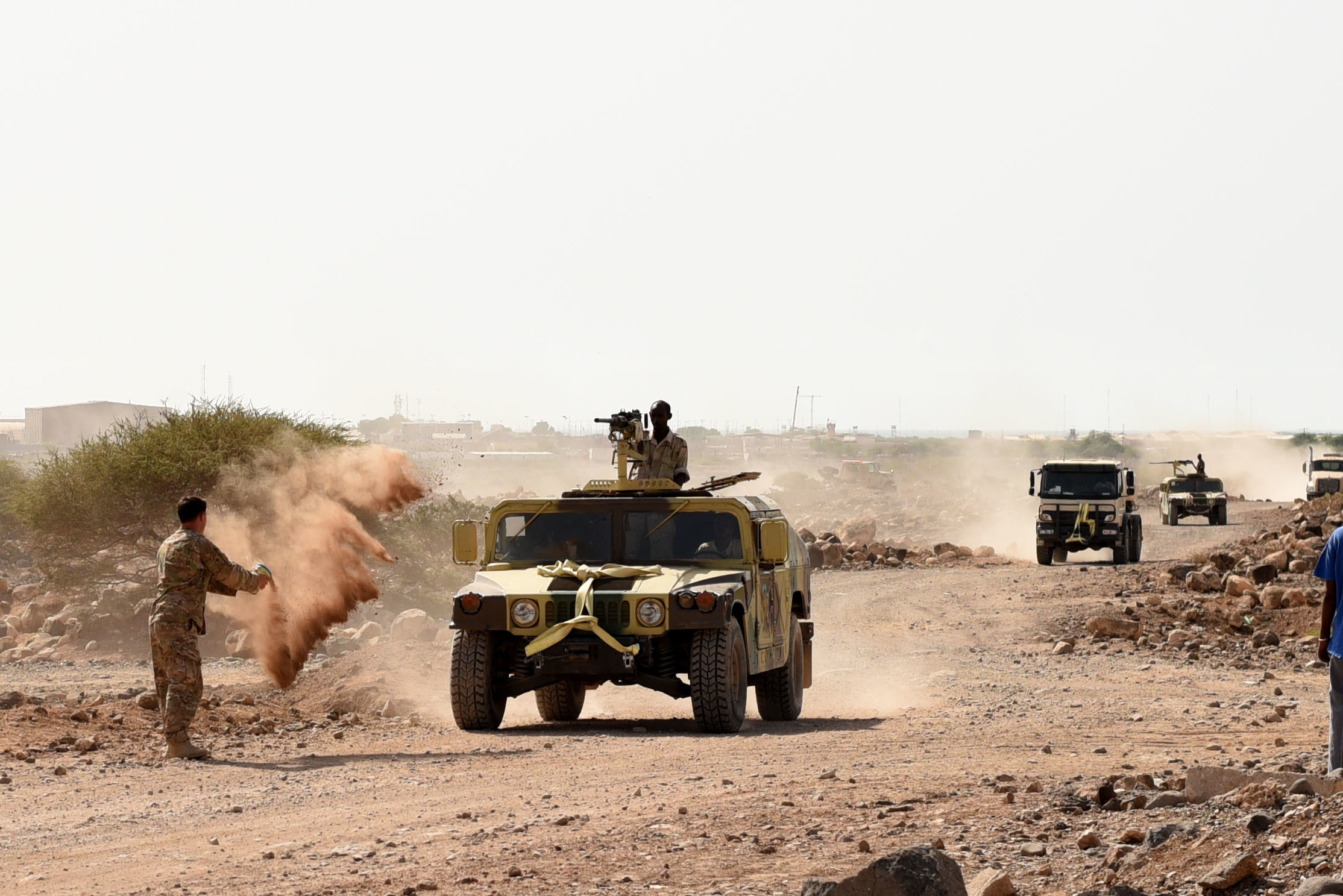 CAMP CHEIK OSMAN, Djibouti – U.S. Army Sgt. Robert Shelton, U.S. Army Regionally Aligned Forces instructor, throws dirt at a Humvee to simulate a roadside detonation causing immobility during Area Logistics Training final with Djiboutian Armed Forces (FAD) soldiers, May 16, 2016, at Camp Cheik Osman, Djibouti. The FAD soldiers tested combat skills they learned throughout the five month course demonstrating their reactions to various mock situations from convoying through a road block, identifying mock roadside bombs, medical care, and vehicle recovery. (U.S. Air Force photo by Staff Sgt. Tiffany DeNault/Released)