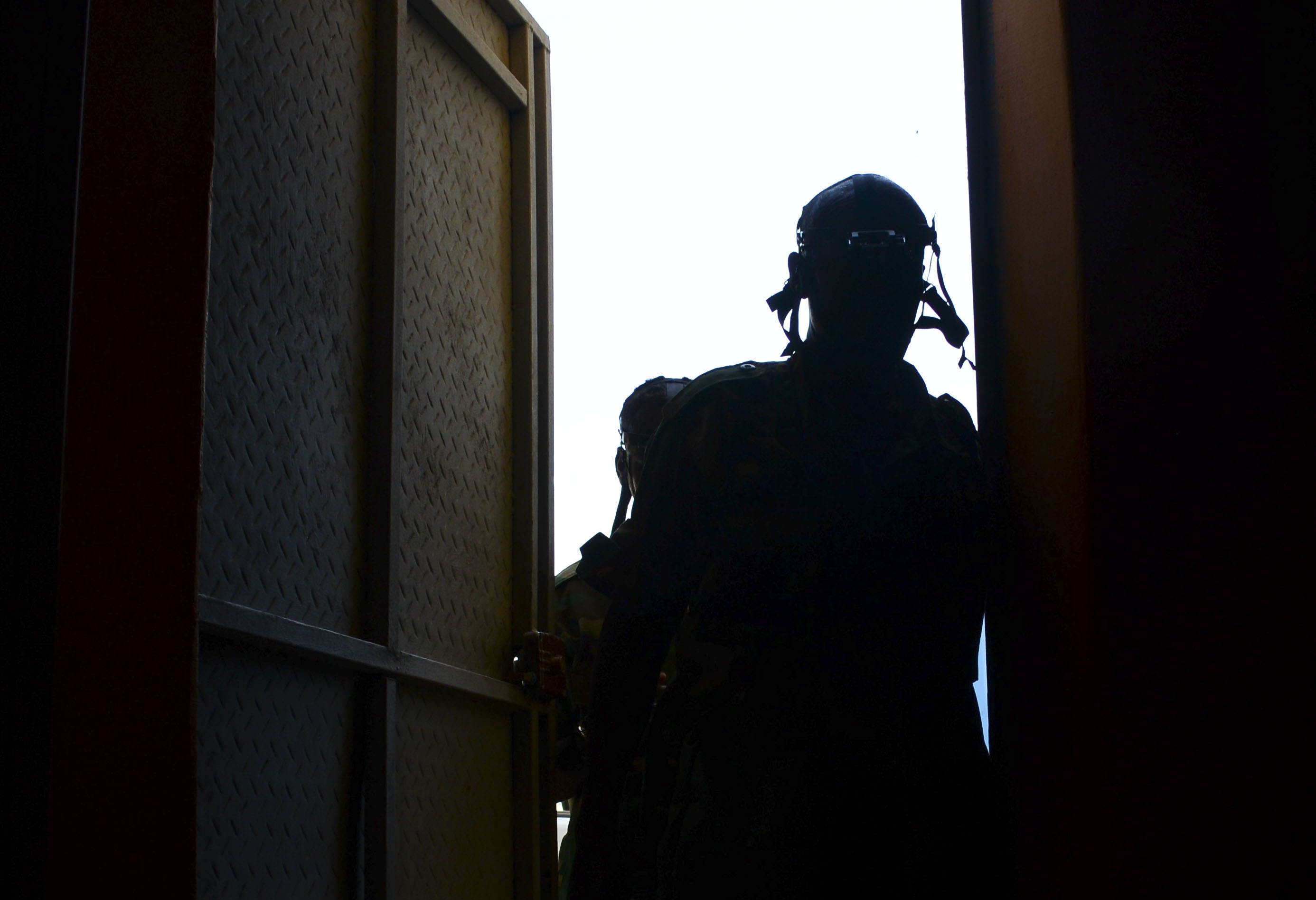 A Djiboutian soldier enters a dark building during a night vision goggle training exercise in Djibouti City, Djibouti, Oct. 10, 2016. During the exercise, the soldiers worked in small teams to navigate obstacles in a dark room to find a designated object and bring it back outside the building. (U.S. Air Force photo by Staff Sgt. Benjamin Raughton)
