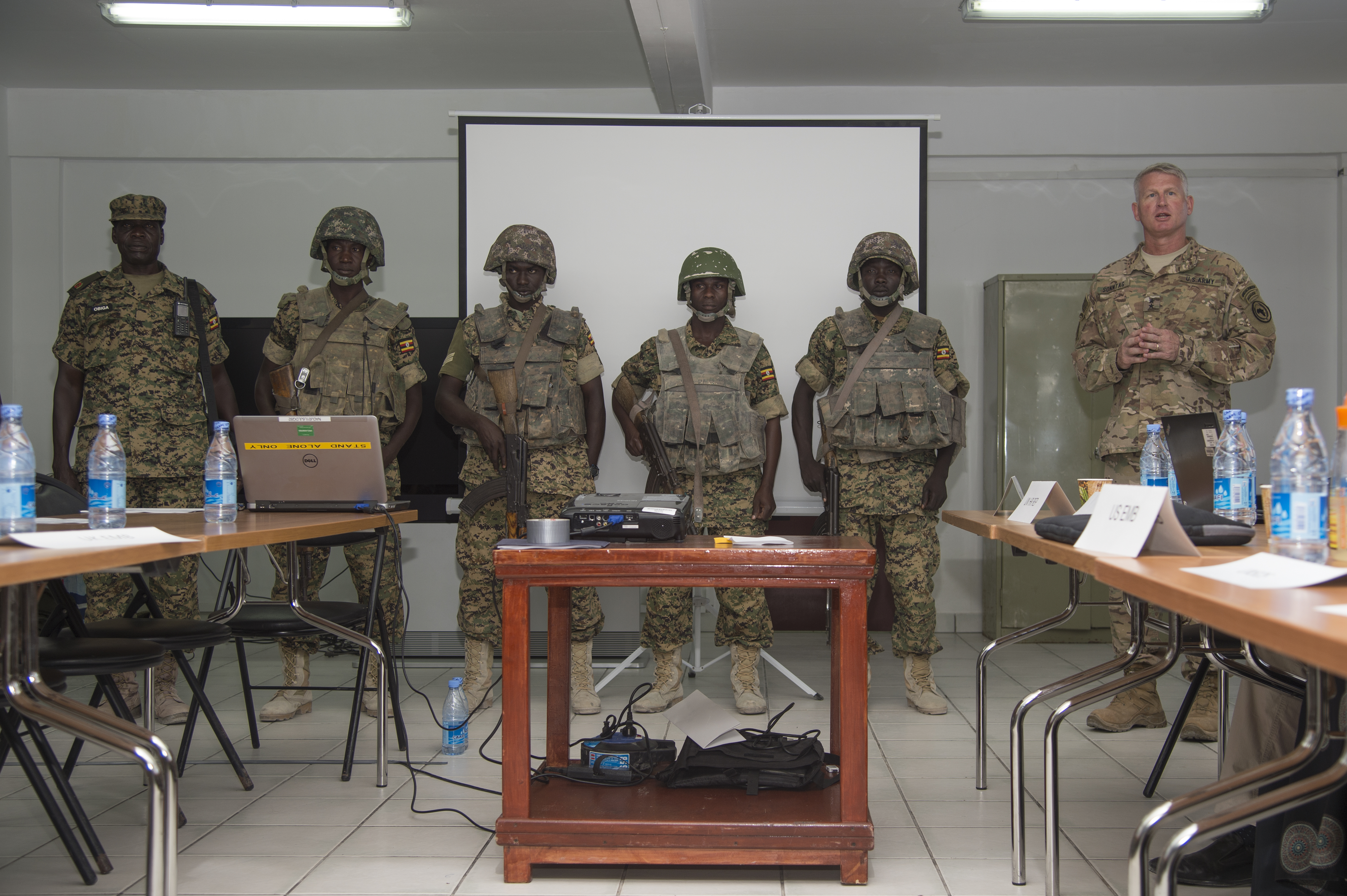 Maj. Gen. Kurt Sonntag, commanding general of the Combined Joint Task Force-Horn of Africa, right, recognizes members of the Ugandan military responsible for defeating a vehicle borne IED attack while serving with the African Union Mission in Somalia during the SNA Symposium in downtown Mogadishu, Jan. 11, 2017. AMISOM is an active, regional peacekeeping mission operated by the African Union with the approval of the United Nations in Somalia. (Photo by  Master Sgt. Paul Gorman/Released)
