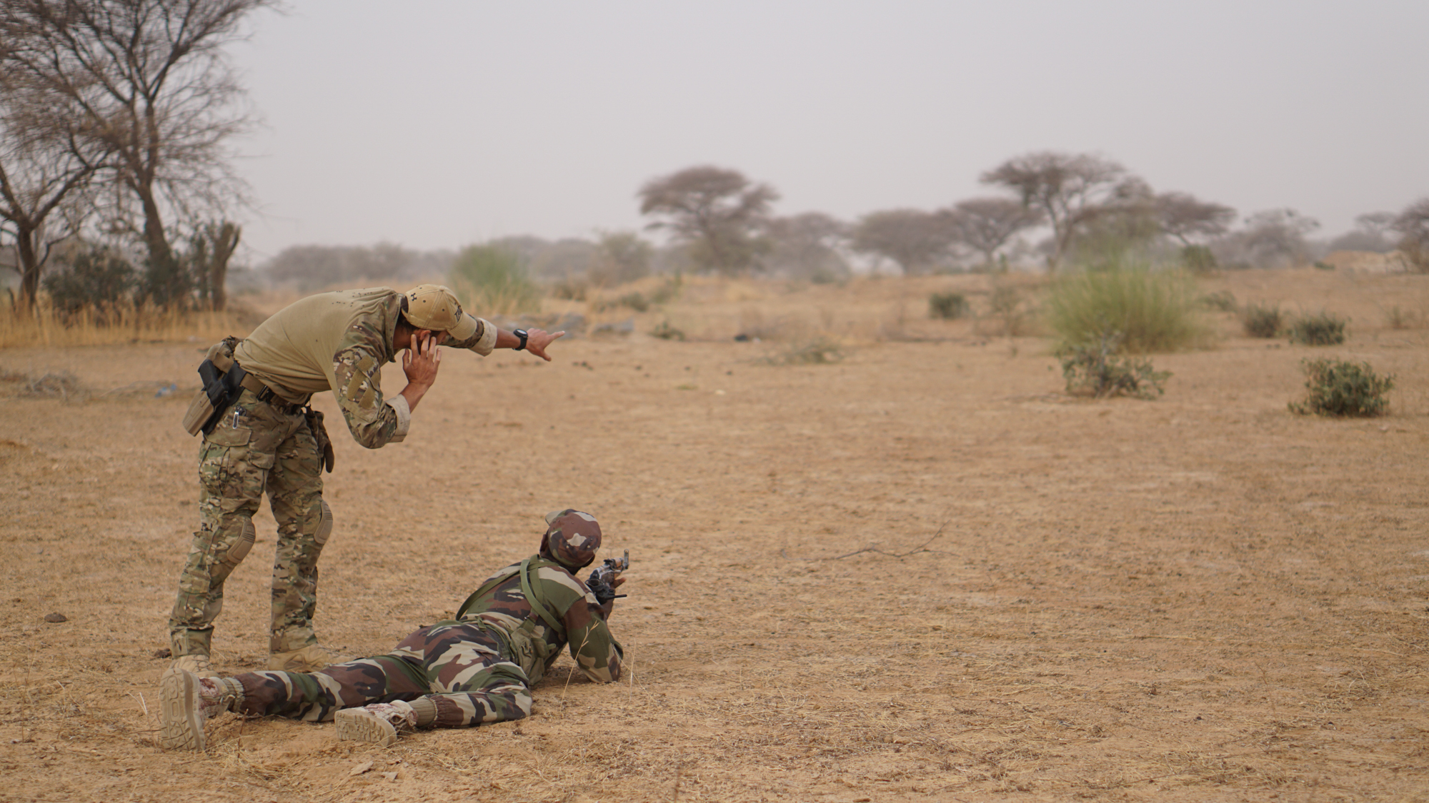 A Belgian Special Operations Forces service member shows a Nigerien soldier his sector of fire while reacting to contact on a dismounted patrol during Exercise Flintlock 2017 in Diffa, Niger, March 11, 2017. Flintlock bolsters partnerships between African, European and North American Special Operations Forces which increases their ability to work together in response to crises. (U.S. Army photo by Spc. Zayid Ballesteros/Released)