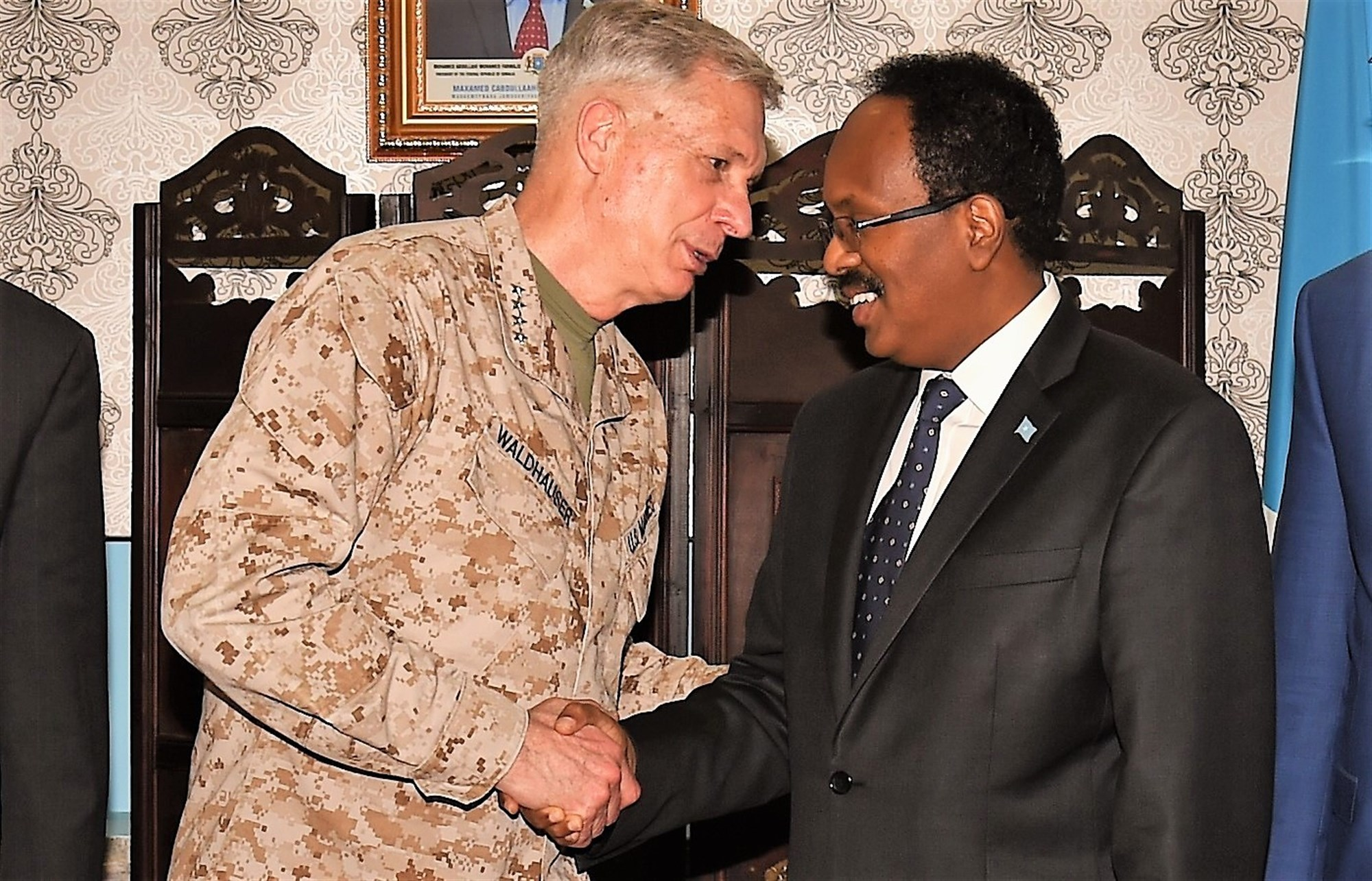 "U.S. Africa Command commander U.S. Marine Corps Gen. Thomas D. Waldhauser, and President of Somalia Mohamed Abdullahi Mohamed, known by his nickname ""Farmaajo,"" shake hands after their meeting held at Mogadishu International Airport, Somalia, April 29, 2017. With its partners, USAFRICOM works to neutralize transnational threats, protect U.S. personnel and facilities, prevent and mitigate conflict, and build defense capability to promote regional stability and prosperity. (U.S. Air National Guard photo by Tech. Sgt. Andria Allmond/Released)"