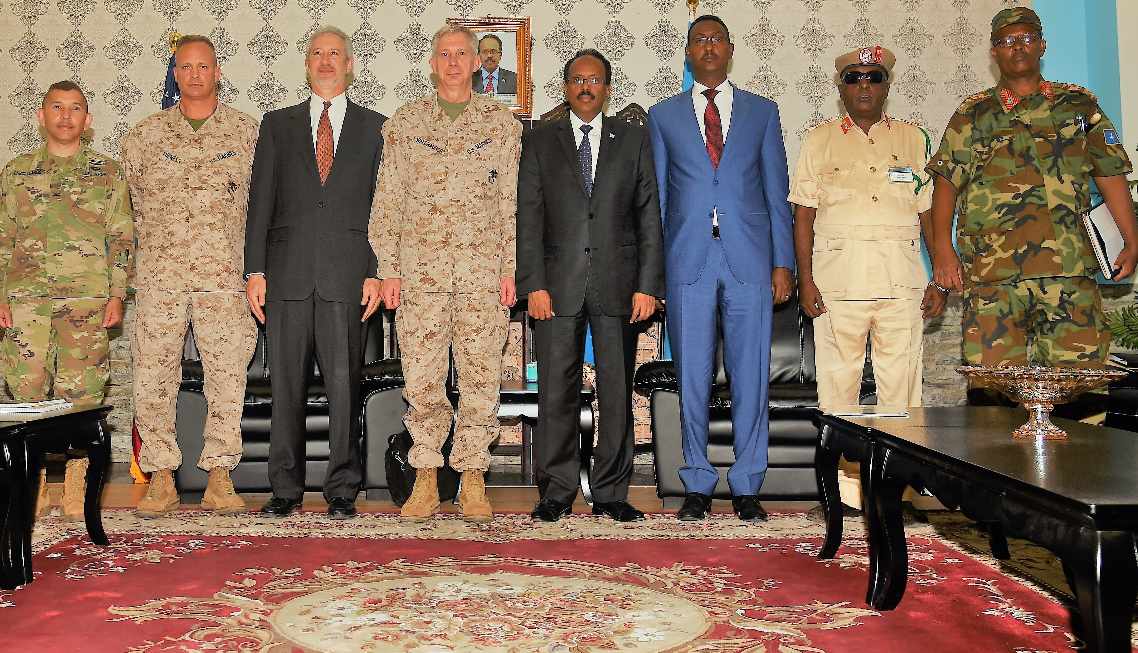 "U.S. Africa Command commander U.S. Marine Corps Gen. Thomas D. Waldhauser, U.S. and President of Somalia Mohamed Abdullahi Mohamed, known by his nickname ""Farmaajo,"" stand alongside their respective dignitaries and military coterie after their meeting held at Mogadishu International Airport, Somalia, April 29, 2017. With its partners, USAFRICOM works to neutralize transnational threats, protect U.S. personnel and facilities, prevent and mitigate conflict, and build defense capability to promote regional stability and prosperity. (U.S. Air National Guard photo by Tech. Sgt. Andria Allmond/Released)"