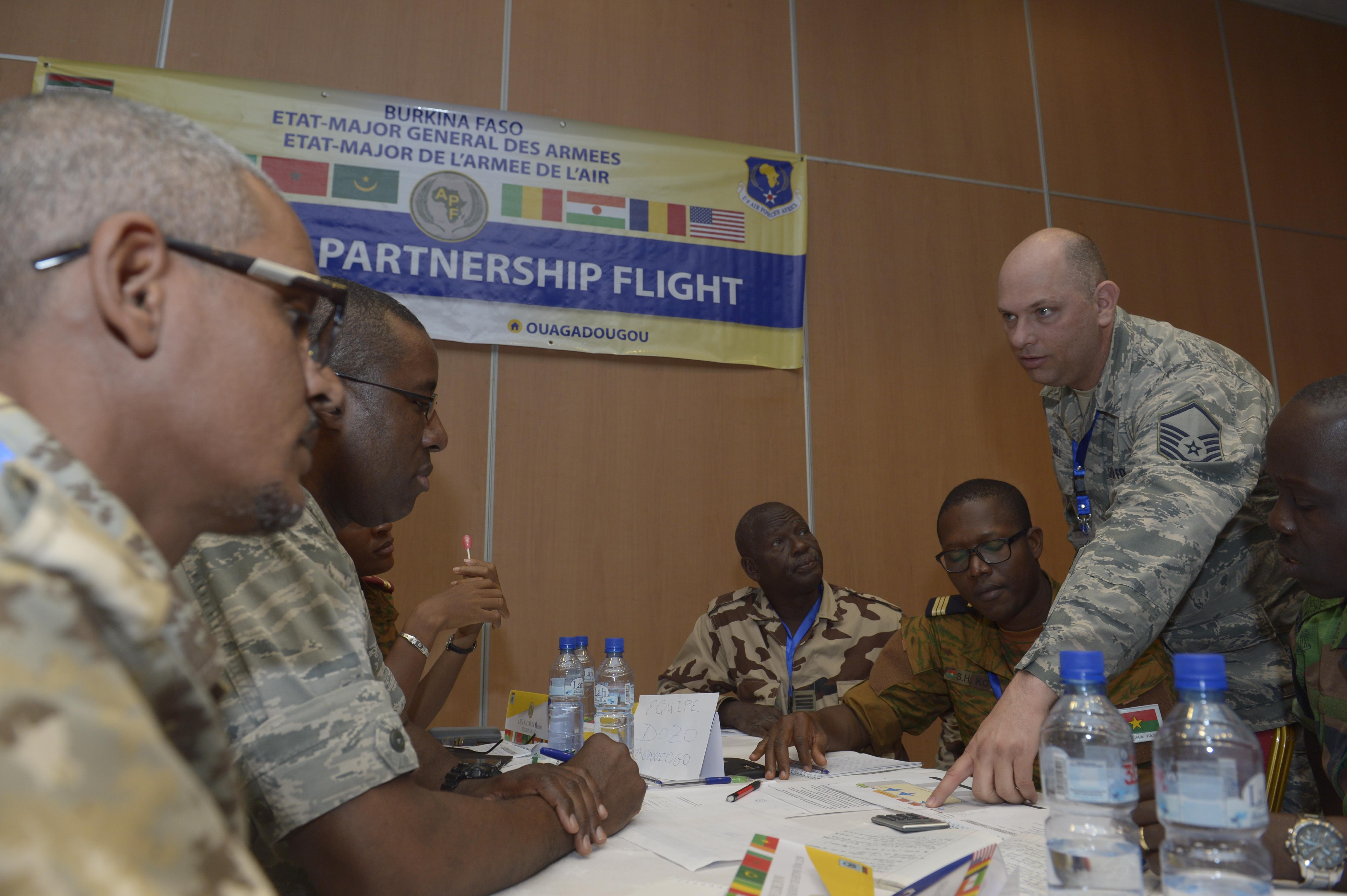 U.S. Air Force Master Sgt. Johnny Hall, right, 818th Mobility Support Advisory Squadron air advisor aircraft maintenance, talks with African Partnership Flight participants during a table top workshop in Ouagadougou, Burkina Faso, April 20, 2017. The intent of APF is to build strong transparent partnerships that enhance regional stability and security through formal alliances, partnerships and simple exchanges of information. (U.S. Air Force photo by Staff Sgt. Jonathan Snyder)