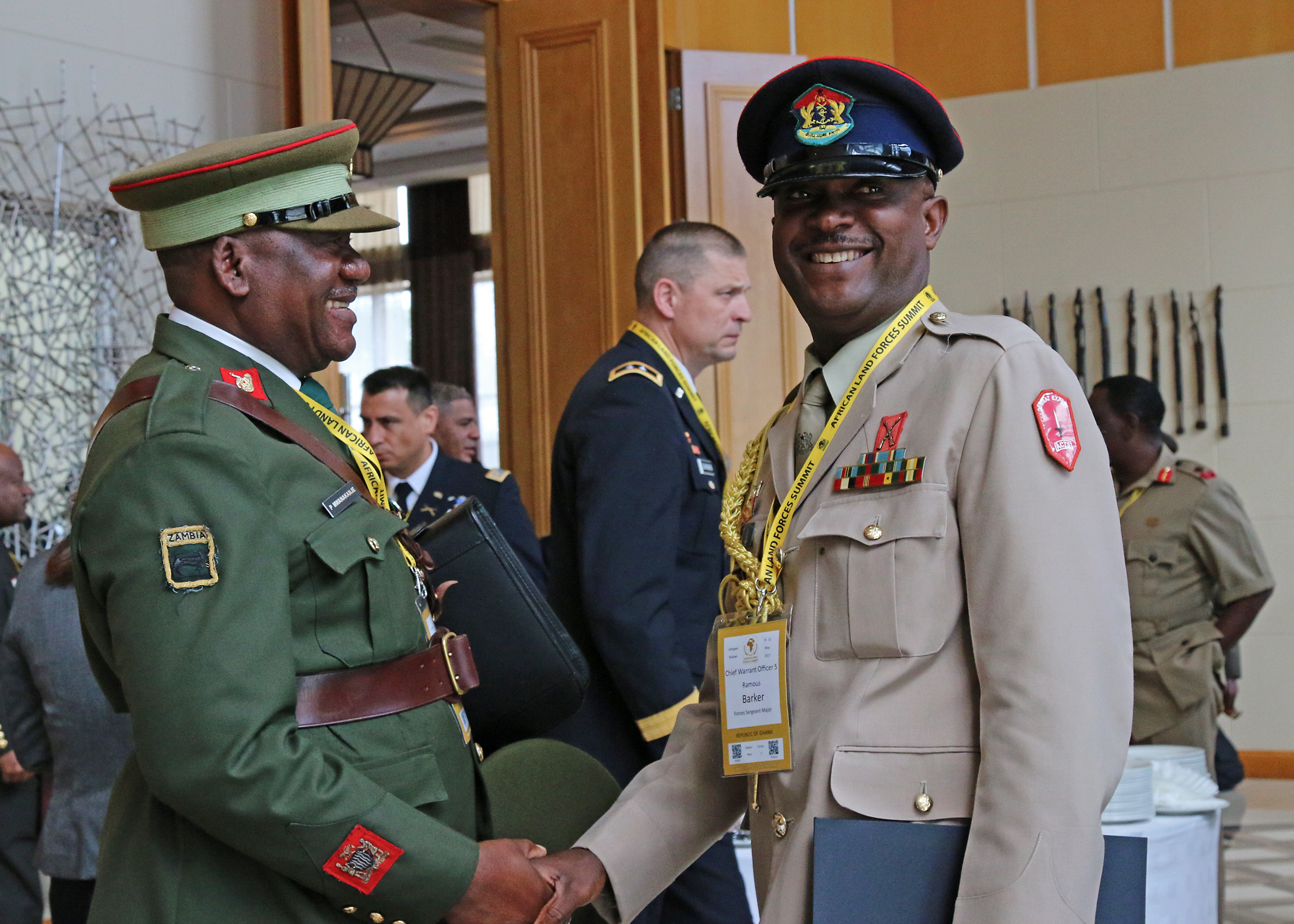 Warrant Officer 1 Patson Mwanakanje (left), a member of the Zambian Army headquarters, and Chief Warrant Officer 5 Ramous Barker, Republic of Ghana Forces Sergeant Major, socialize during the African Land Forces Summit, in Lilongwe, Malawi, May 11, 2017. ALFS is an annual, weeklong seminar bringing together land force chiefs from across Africa for candid dialog to discuss and develop cooperative solutions to regional and transregional challenges and threats. (U.S. Army photo by Sgt. Paige Behringer/Released)