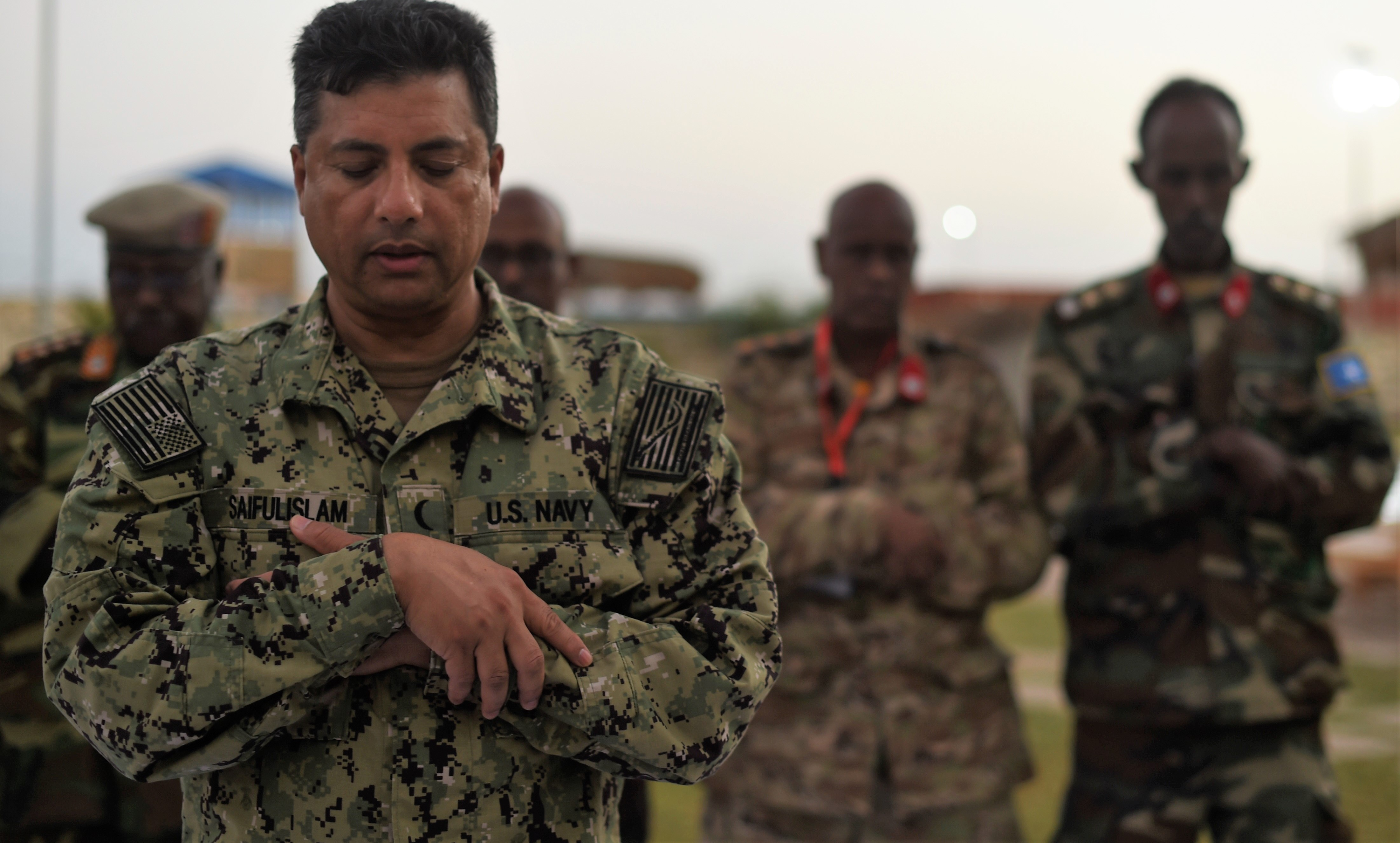 U.S. Navy Cmdr. Abuhena Saifulislam, U.S. Africa Command deputy command chaplain, leads a prayer before an Iftar with members of the Somali National Army at the Mogadishu International Airport, Mogadishu, Somalia, June 5, 2017. This was the first Iftar held between U.S. and SNA military personnel. Additionally, it was the first led by a U.S. Imam, who is a leader in the Islamic faith.(U.S. Air Force Photo by Staff Sgt. Eboni Prince/Released)