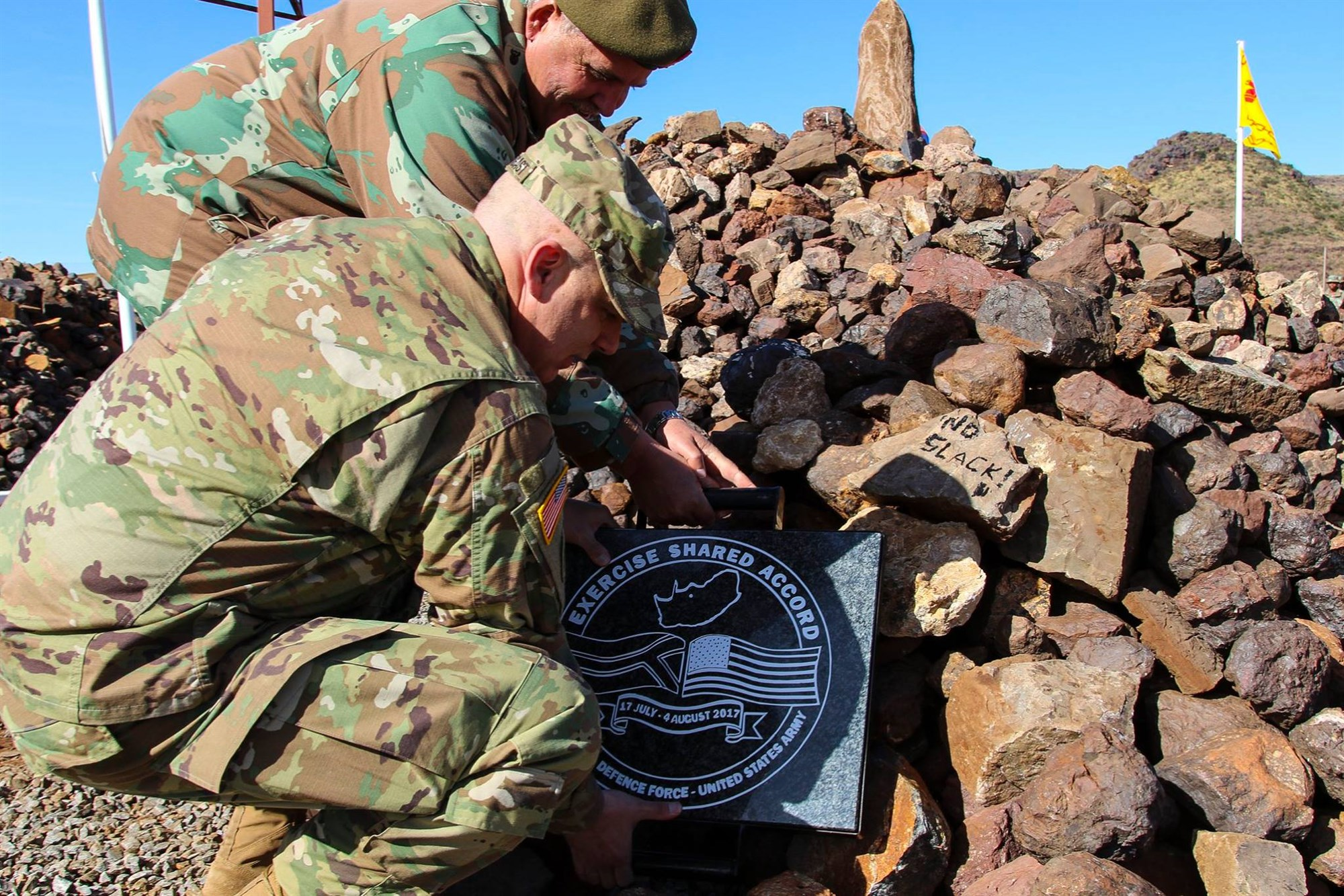 South African Army Brig. Gen. Gustav Lategan and Brig. Gen. William J.Prendergast, U.S. Army Africa Deputy Commanding General, places the final plaque on the pile of rocks signifying the pledge to train safely during Shared Accord 2017 at the South Africa Army Combat Training Center, July 17, 2017. SA17 is a Joint-Combined Command Post Exercise (CPX) and company field training exercise (FTX) focused on peace keeping operations designed to exercise participants' capability and capacity to conduct African Union/United Nations mandated peace keeping operations.
