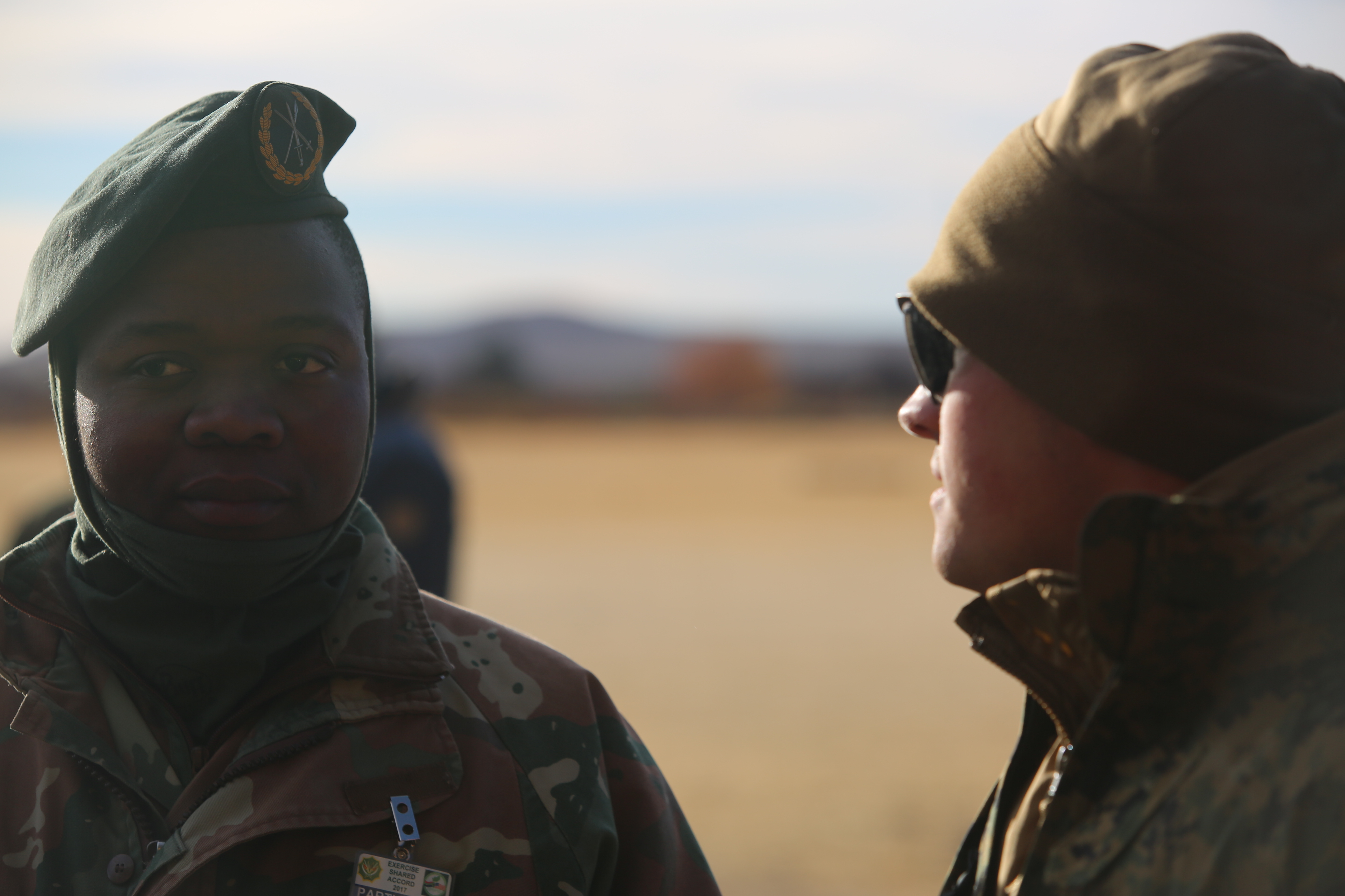 A member of the South African Army talks to and builds comraderie with a U.S. Marine during a break in training classes as part of Shared Accord 17 (SA17) at South African Army Combat Training Center, Lohatla, South Africa, July 17, 2017. SA17 is a Joint bi-lateral Field Training Exercise with our South African partners focused on Peace Keeping Operations designed to exercise participants' capability and capacity to conduct African Union / United Nations mandated Peace Keeping Operations.