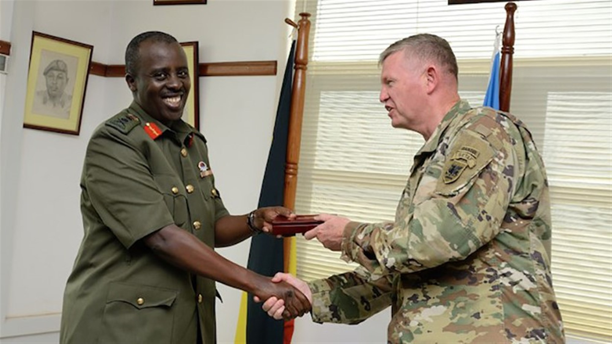 KAMPALA, Uganda -- U.S. Army Africa Commander Maj. Gen. Joseph P. Harrington, right, exchanges gifts with Gen. David Muhoozi, the Uganda People's Defense Force chief of defense forces, in Kampala, Uganda, July 31, 2017. The senior leaders discussed initiatives to improve long-term security capacity in the region. (Photo courtesy of U.S. Embassy Kampala)