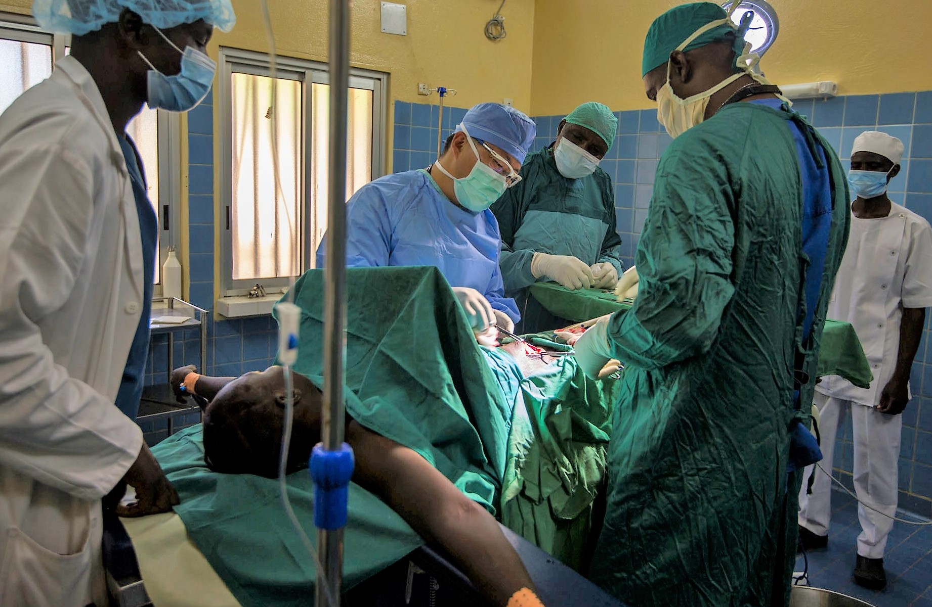 U.S. Army Maj. Joseph Lee, center, a general surgeon assigned to 212th Combat Support Hospital, assists Cameroonian Lt. Col. Sebastien Mvogo, right, a general surgeon, perform an appendectomy at the Regional Hospital of Garoua during Medical Readiness Training Exercise 17-5 in Garoua, Cameroon, Aug. 8, 2017. The mutually beneficial exercise, being conducted for the first time in the region, offers opportunities for the partnered militaries to share best practices and improve medical treatment processes. (U.S. Army Africa photo by Staff Sgt. Shejal Pulivarti)