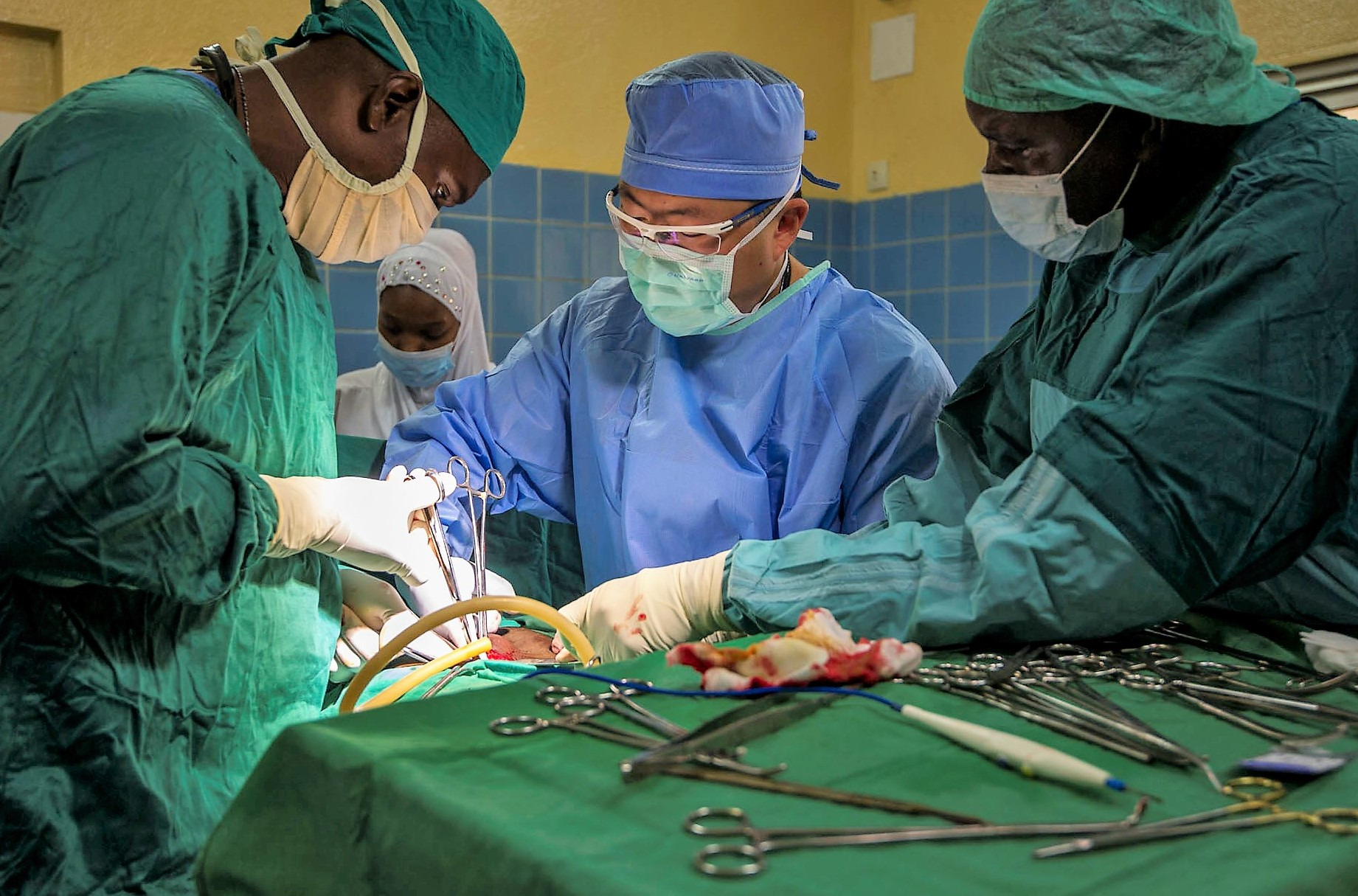 Cameroonian Lt. Col. Sebastien Mvogo, left, a general surgeon, and U.S. Army Maj. Joseph Lee, center, a general surgeon assigned to 212th Combat Support Hospital,perform an  appendectomy at the Regional Hospital of Garoua during Medical Readiness Training Exercise 17-5 in Garoua, Cameroon, Aug. 8, 2017. The mutually beneficial exercise, being conducted for the first time in the region, offers opportunities for the partnered militaries to share best practices and improve medical treatment processes. (U.S. Army Africa photo by Staff Sgt. Shejal Pulivarti)